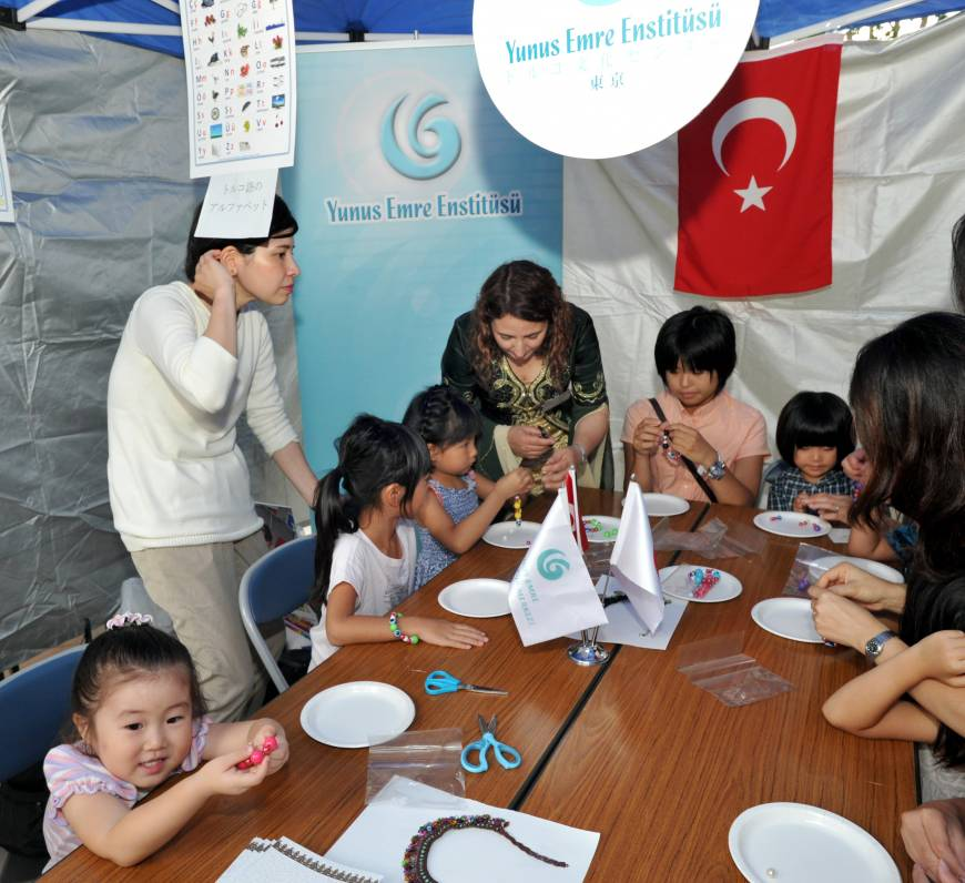 Children make bracelets with Turkish beads at the Turkish embassy booth.
