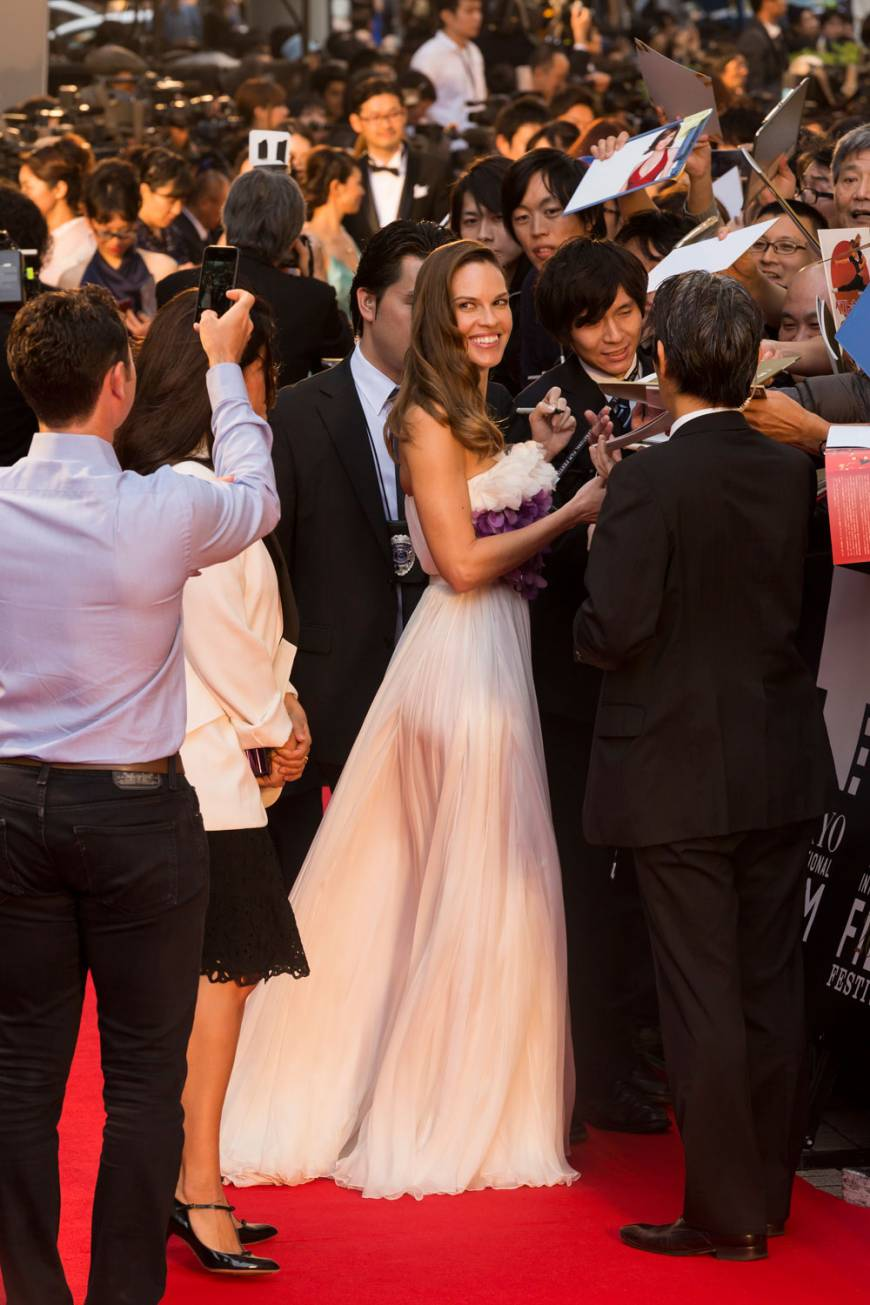 Hilary Swank pauses to sign autographs and to pose for photos during her red carpet stroll at the opening of the 2015 Tokyo Film Festival.