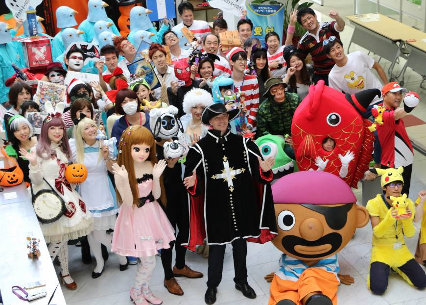 Japanese toy company Tomy president Harold Meij (dressed as a musketeer) and employees clad in costumes pose as they gather for the company