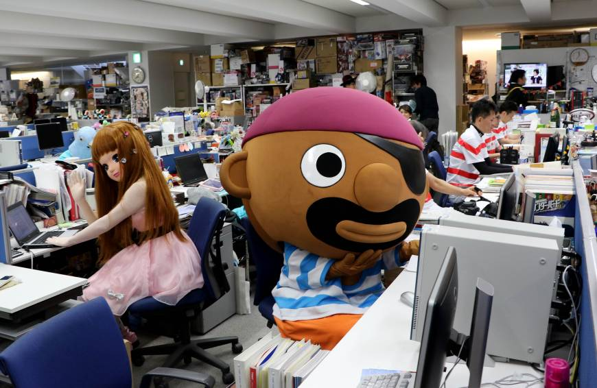 Employees dressed as Licca-chan doll and Pop-up Pirate as they work at their desks.