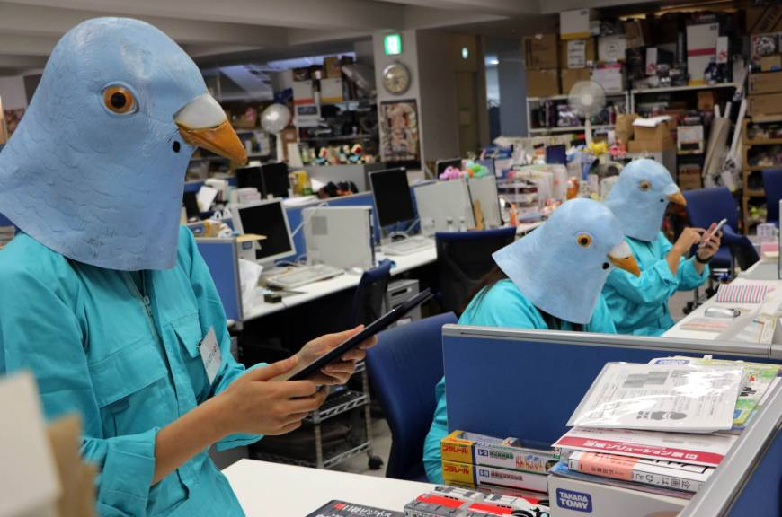 Employees dressed as Twitter birds work at their desks during the company