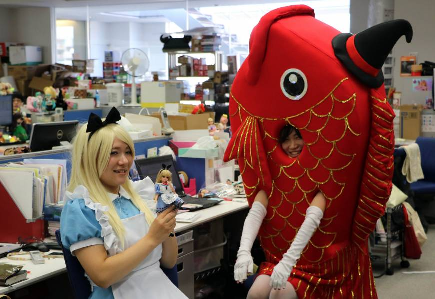 Employees of Japanese toy company Tomy dressed up as characters for Halloween. Pictured are Alice and a large fish wearing a hat seen at their desks during the company