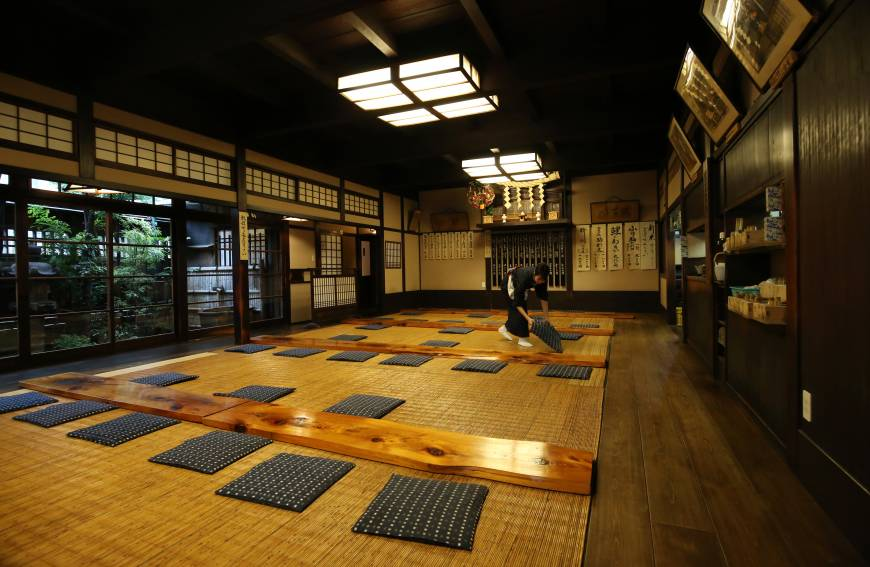 A worker prepares the dining room of Komakata Dozeu for another day of business.