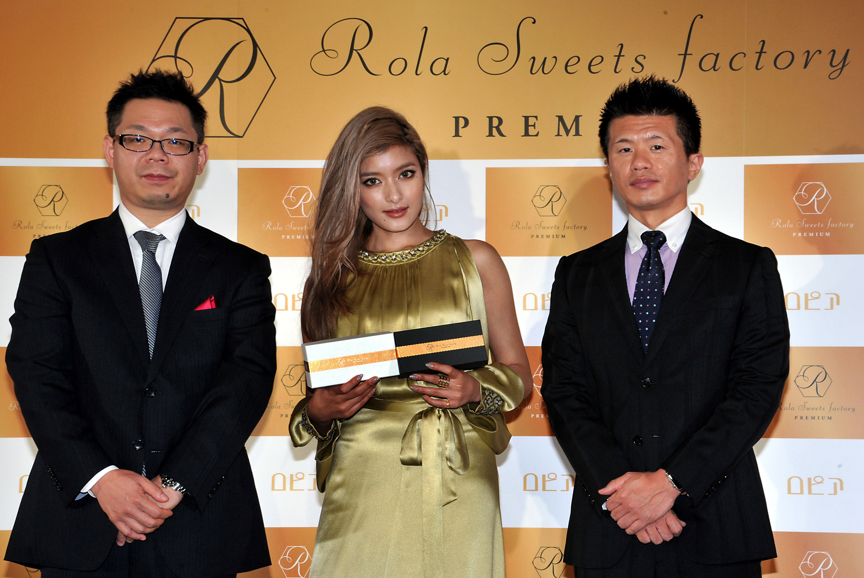 """Model and TV personality Rola (center) holds """"Rola Sweets factory PREMIUM"""" gateau chocolat and white chocolate cakes during a press conference announcing their release, with collaborating company, ROPIA Ltd., President Eiji Takai (left) and Managing Director Hajime Kawai at Arkangel Daikanyama in Tokyo on Dec. 15. (www.rolasweetsfactory.jp) 