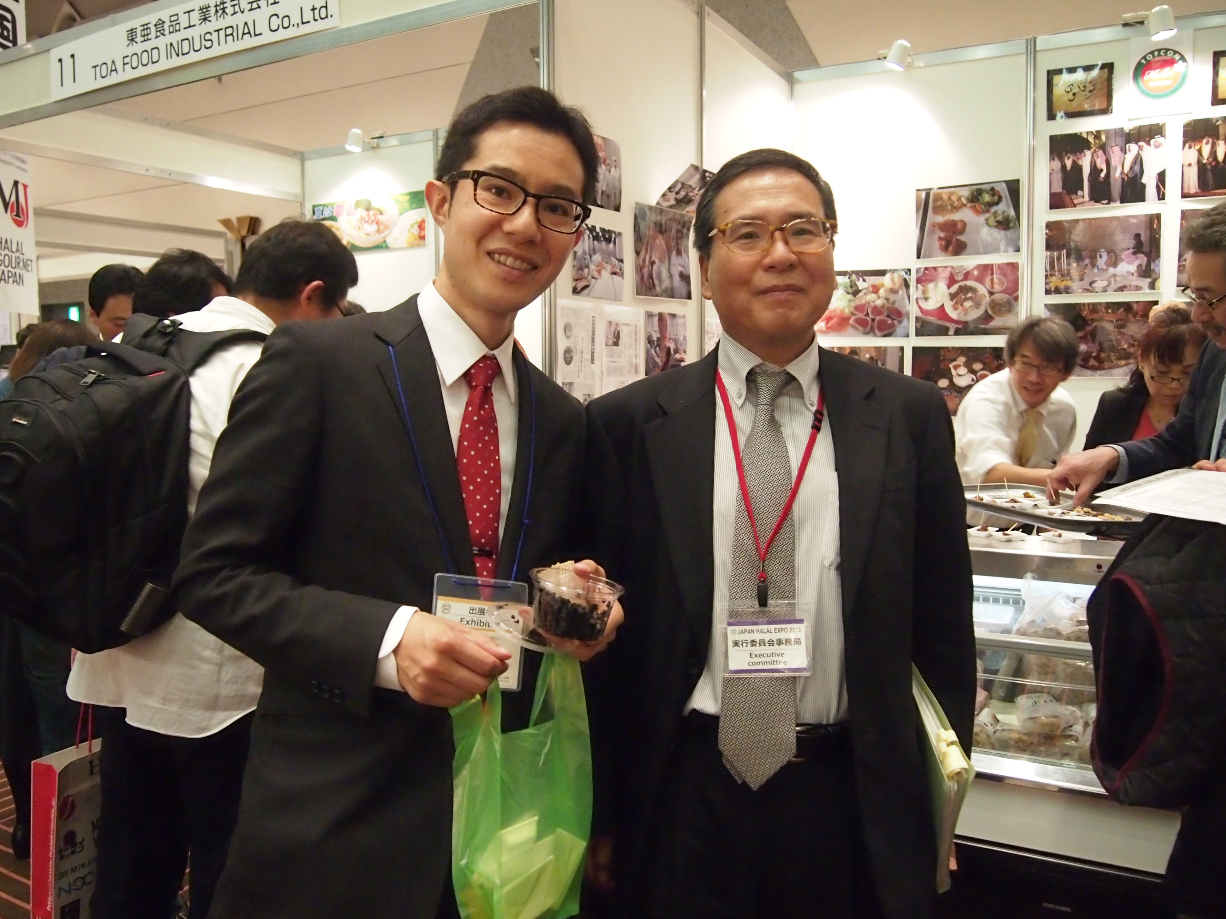 Yoshichika Terasawa (right), of the Japan Halal Expo 2015 executive committee and special advisor to Makuhari Messe Inc. poses with exhibitor Junya Machiya, president of Tenmabayashi Ryutukako from Aomori Prefecture at the event, which saw 67 exhibitors participate, at Makuhari Messe, Chiba Prefecture.   EDLEEN OTHMAN