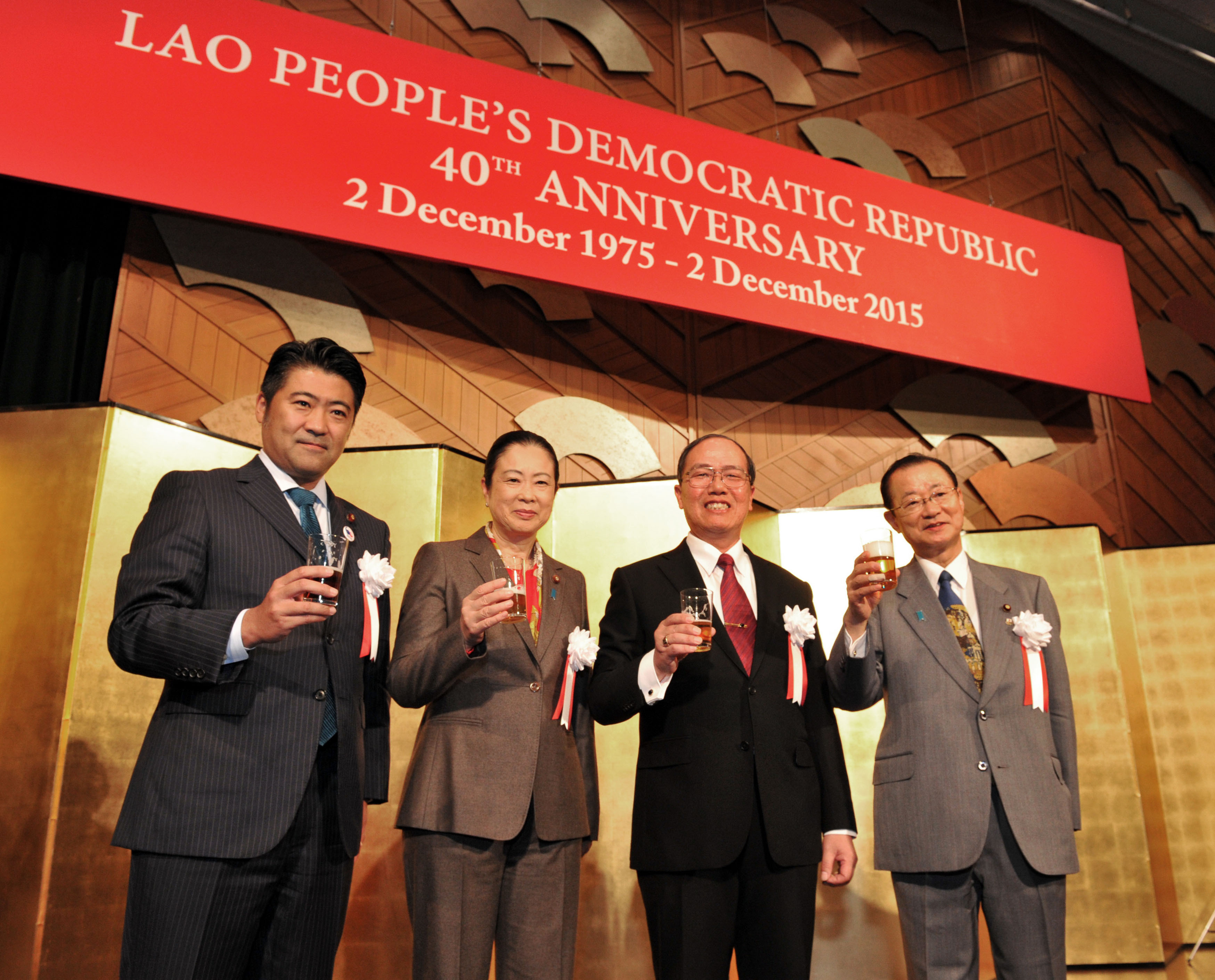 Lao People's Democratic Republic Ambassador Khenthong Nuanthasing (second from right) shares a toast with (from left) State Minister for Foreign Affairs Seiji Kihara; Chairman of the Committee on Foreign Affairs of the House of Representatives Shinako Tsuchiya; and Chairman of the Japan-Laos Parliamentary Friendship League Takeo Kawamura during a reception to celebrate the country's 40th Anniversary of the National Day, at the Hotel New Otani Tokyo on Dec. 3. |  YOSHIAKI MIURA