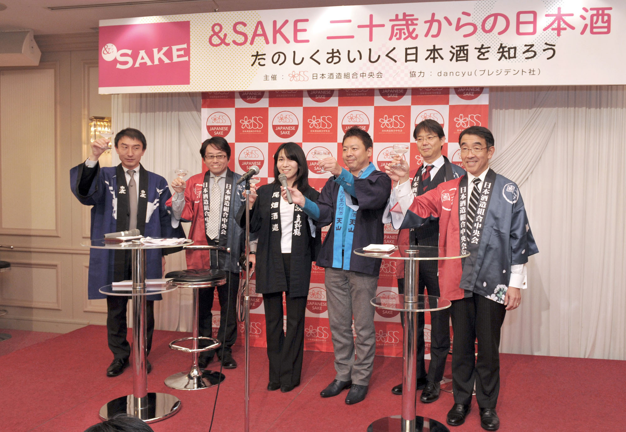 Koichi Saura (right), president of Saura Co. and chairman of the sake sales promotion committee of the Japan Sake and Shochu Makers Association, along with representatives of the sake industry and committee members, share a toast to kick off an event featuring sake tasting, cooking and education for about 100 twenty-year-olds celebrating Coming-of-Age Day. | YOSHIAKI MIURA