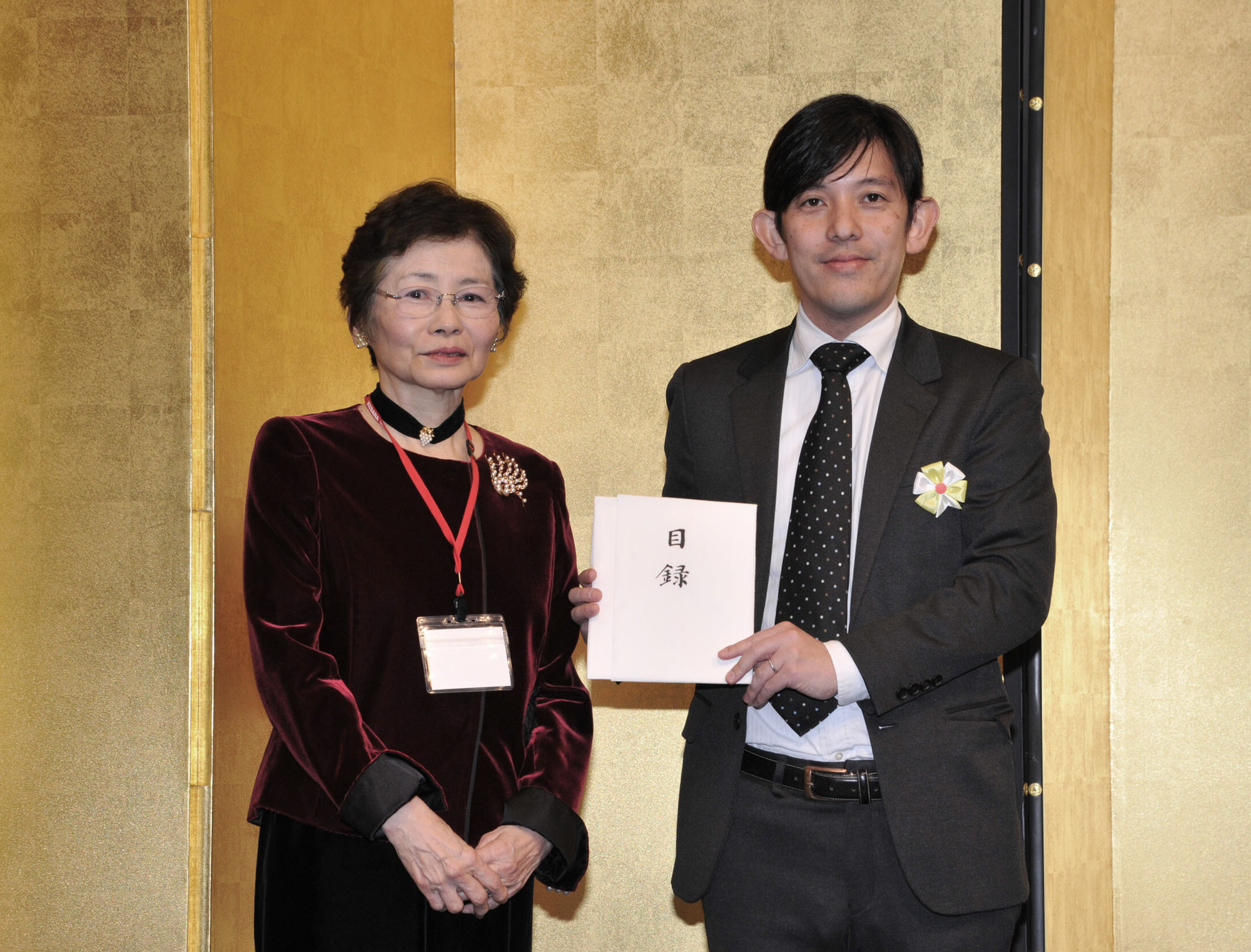 The Japan Times Deputy Sales Officer Yusuke Numata (right) holds a donation to The Japan Times Readers' Fund received from President of Ikebana International Tokyo Founding Chapter Noriko Kira at the Palace Hotel Tokyo on Jan. 26. |  YOSHIAKI MIURA