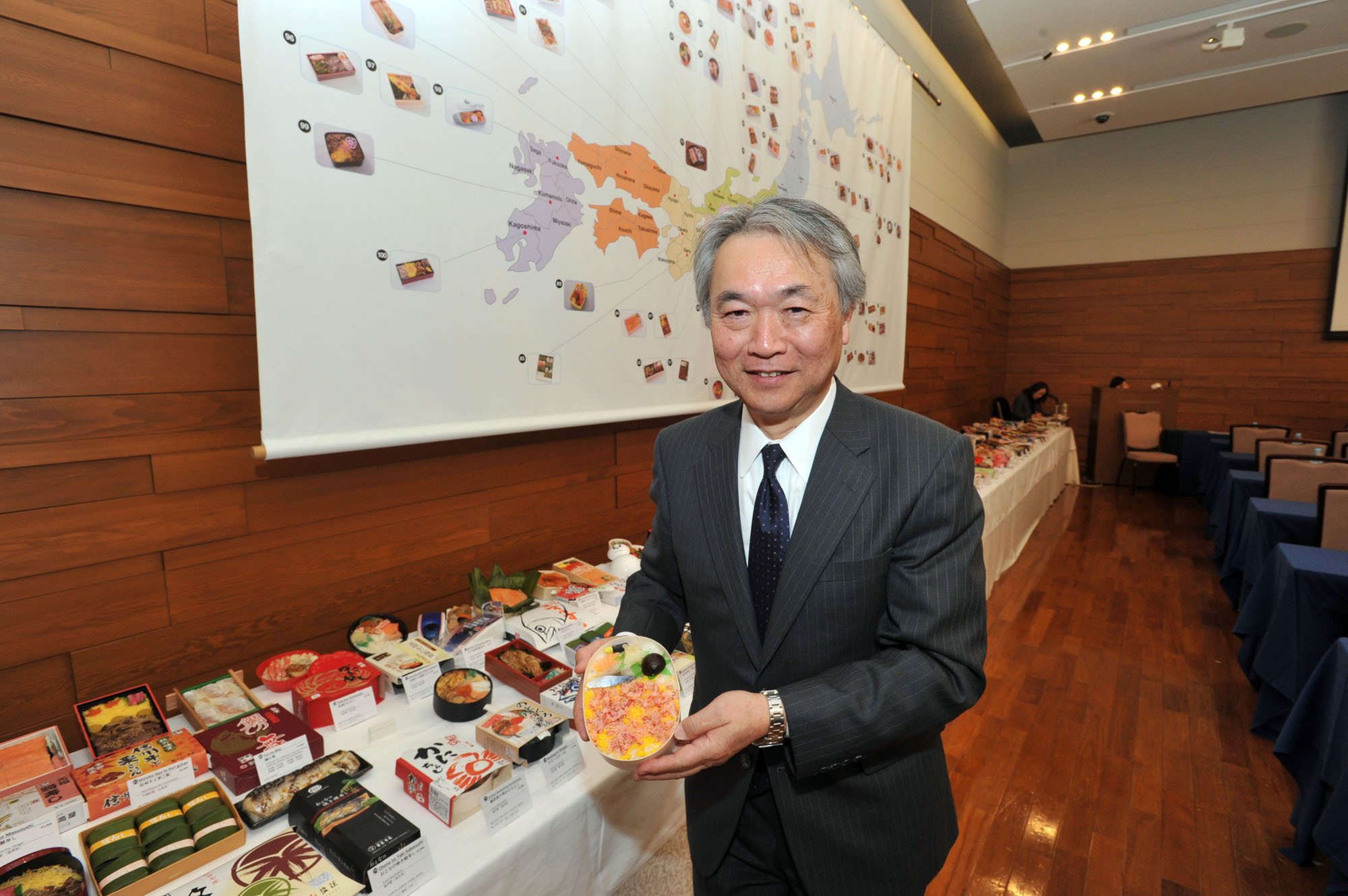 "Noriaki Nakajima, executive director of the Rice Stable Support Organization (Public Interest Incorporated Association) poses with an ekiben (station lunch box) during an event celebrating the 130th anniversary of ekiben, for foreign press in Japan, titled ""The Appeal of 'Ekiben' and 'Rice' Japanese Staple diet.""  
