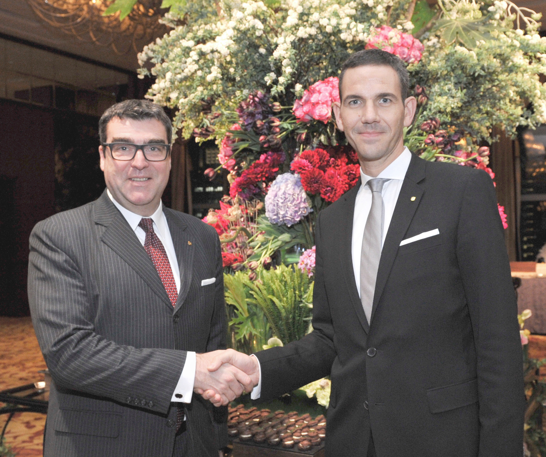 Marcus Bauder (right), the new general manager of the Shangri-La Hotel, Tokyo, shakes hands with outgoing GM Jens Moesker, who is being promoted to area manager and general manager of the Shangri-La Hotel, Toronto, during a reception at the hotel in Tokyo on Feb. 4. | YOSHIAKI MIURA