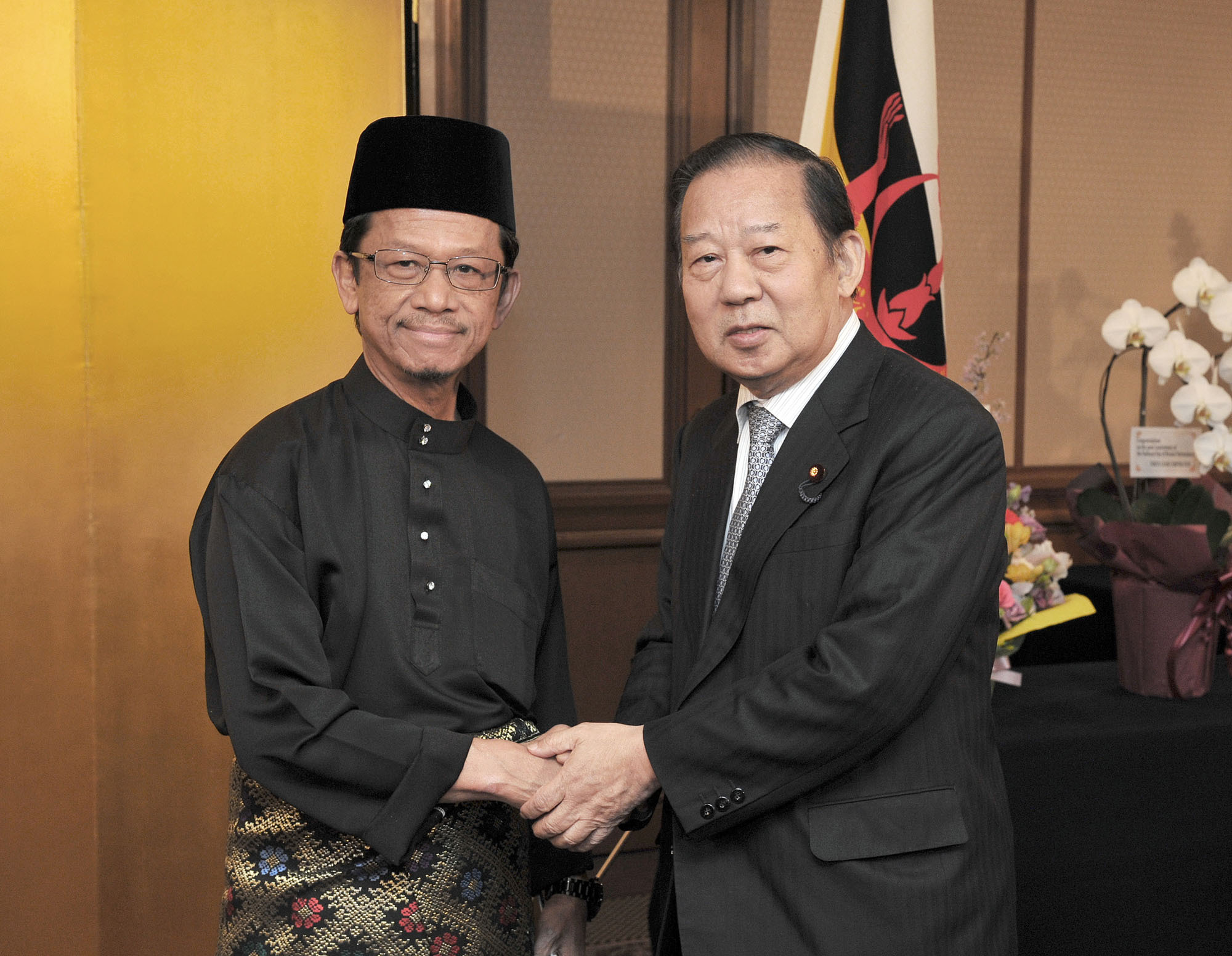 Brunei Ambassador Mahamud Ahmad (left) welcomes Toshihiro Nikai, chairman of the Japan-Brunei Parliamentary Friendship League, to a reception celebrating the 32nd anniversary of the National Day of Brunei Darussalam at the Imperial Hotel, Tokyo on Feb. 23. | YOSHIAKI MIURA