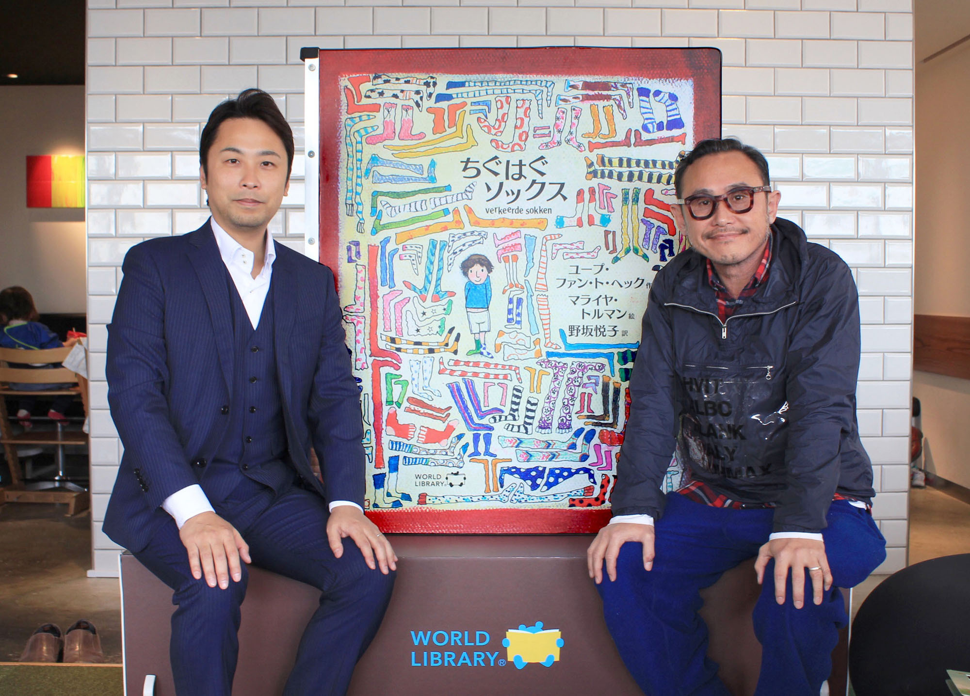 President of Smiles Co. Masamichi Toyama (right) poses with Shinsaku Asano, CEO of World Library, in front of an oversized picture book. The 100 Spoons restaurant in Azamino, Kanagawa Prefecture (operated by Smiles Co.), hosted a storytelling event on March 13 with a foreign book that was translated into Japanese and printed extra large to amuse children. The restaurant is creating opportunities for children to socialize using translated foreign picture books. | WORLDLIBRARY