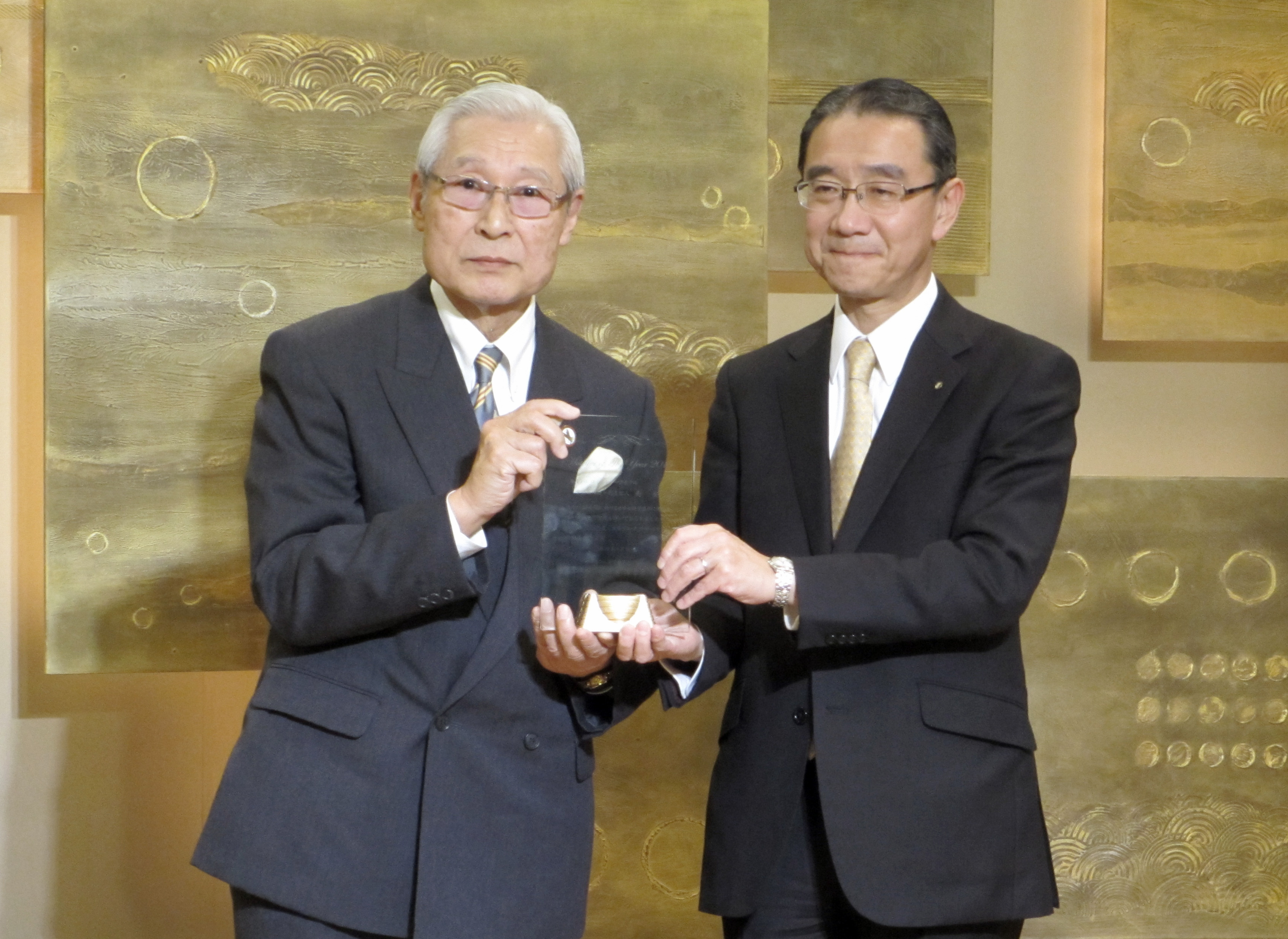 """""""Hotelier of the Year, 2015,"""" Yasushi Minami (right), managing director and general manager of the Royal Park Hotel receives an award recognizing his achievements from Yasunari Ebihara (left), a representative of a hotel industry association, on March 16 at the Royal Park Hotel. 