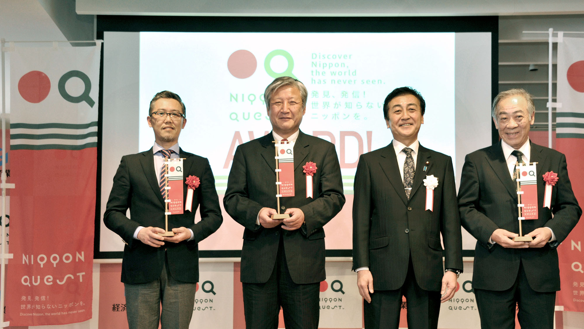 "Economy, Trade and Industry Vice Minister Tsuyoshi Hoshino (second from right) poses with winners of the first Nippon Quest Awards at Marugoto Nippon in Asakusa, Tokyo, on March 4. The awards are given to people who spread information about unique regional items on the Nippon Quest website. (From left) ""Food Specialty"" winner Dainari Goka, who won for Halal Gyoza by Nikkoken; ""Goods Specialty"" winner Seiichi Kimoto, who won for Raven Edo Kiriko; and ""Activity Specialty"" winner Genrokuro Matsunaga, who won for visiting a Japanese sword smith. 