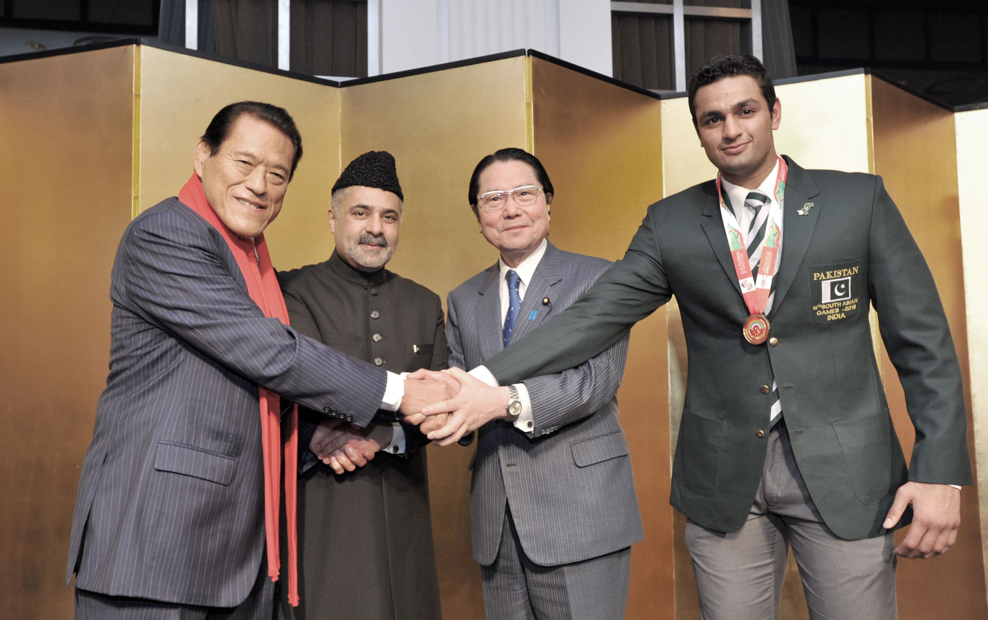 Pakistan Ambassador Farukh Amil (second from left) shakes hands  with, from left, House of Councillors member Antonio Inoki; President of the Japan-Pakistan Parliamentarians' Friendship League Seishiro Eto; and judoka Shah Hussain, a Tsukuba University student and a member of the Pakistan National Judo Team, during a reception to celebrate the country's National Day at the New Otani Hotel in Tokyo on March 23. | YOSHIAKI MIURA
