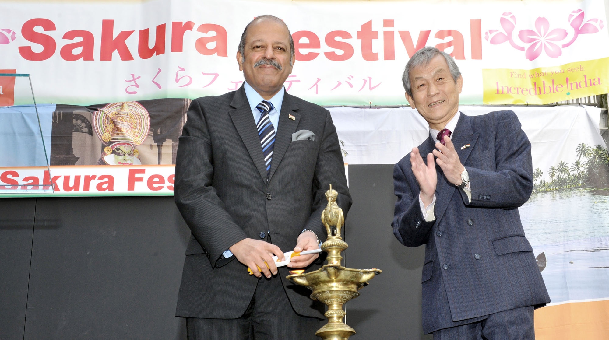 Indian Ambassador Sujan R. Chinoy (left) lights a traditional oil lamp during the opening ceremony of the Sakura Festival 2016, as President of the Japan-India Association Hiroshi Hirabayashi (right) applauds at the embassy in Tokyo on March 25. The sakura festival at the embassy showcases Indian cultural performances, food and handicrafts. | YOSHIAKI MIURA