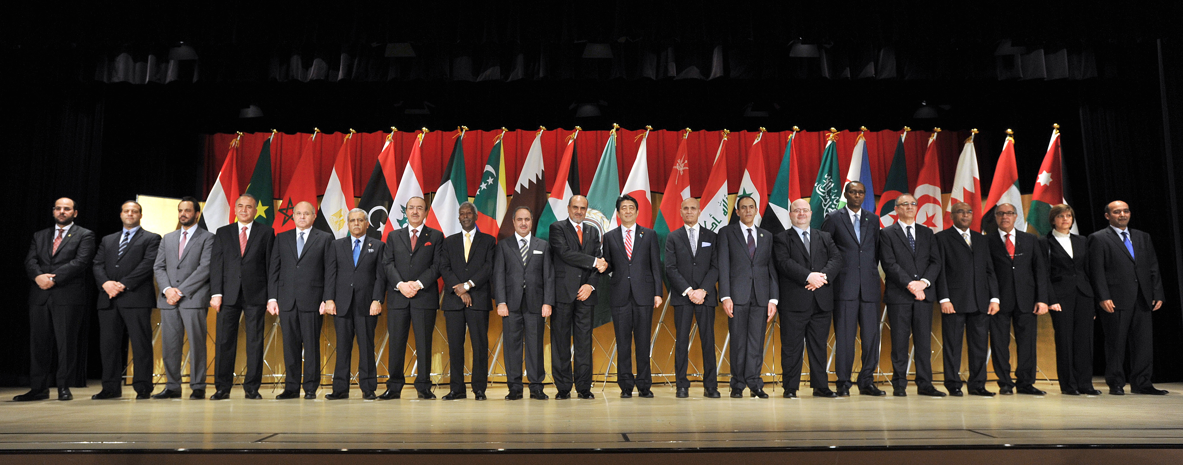 Members of the Council of Arab Ambassadors and Heads of Missions in Japan stand on stage as Prime Minister Shinzo Abe shakes hands with Dean of the Arab Diplomatic Corps Waleed Siam at the Imperial Hotel, Tokyo on April 4. | YOSHIAKI MIURA