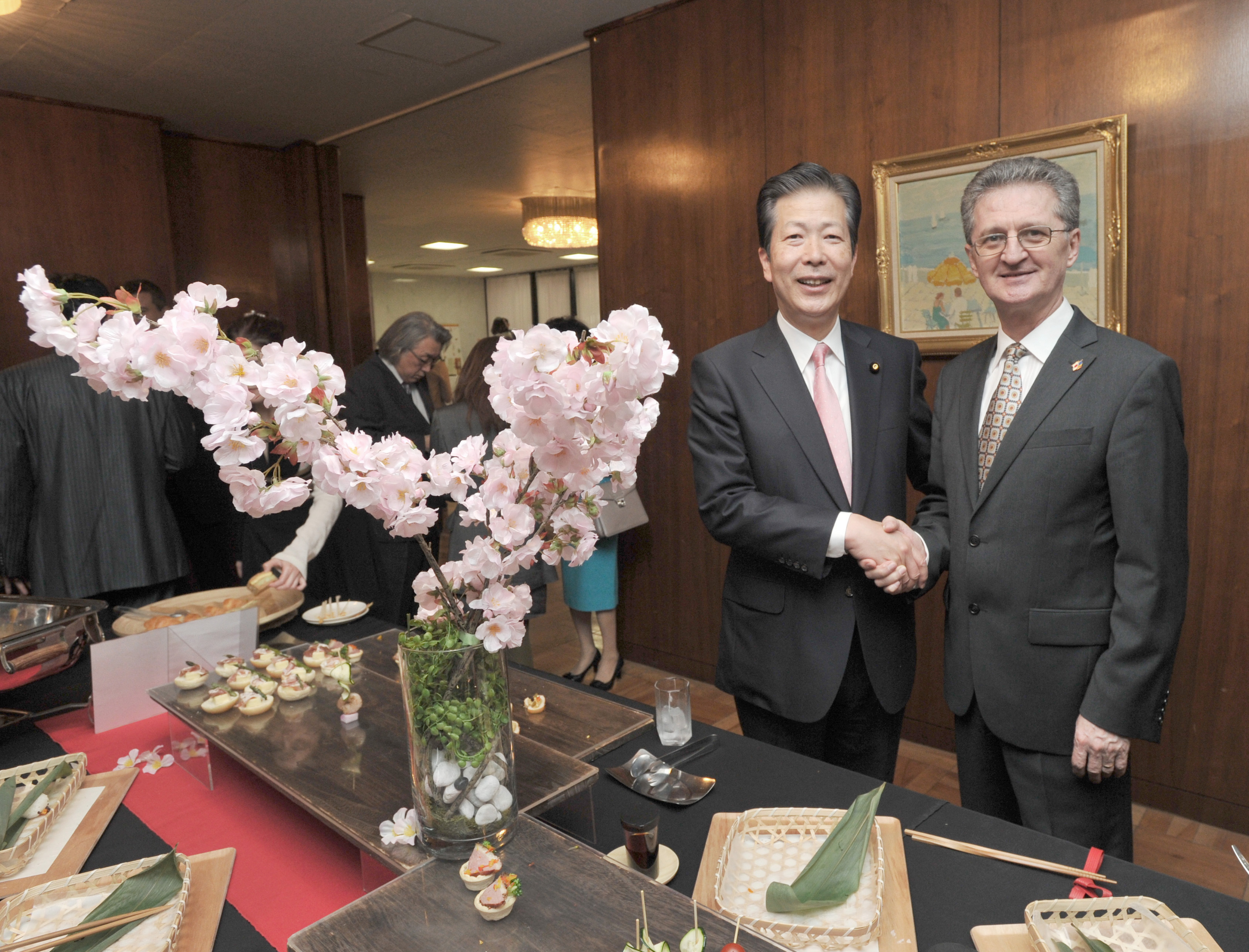 Romanian Ambassador Radu Serban (right) shakes hands  with Komeito leader Natsuo Yamaguchi during a cherry blossom viewing party at the embassy in Tokyo on March 30. | YOSHIAKI MIURA