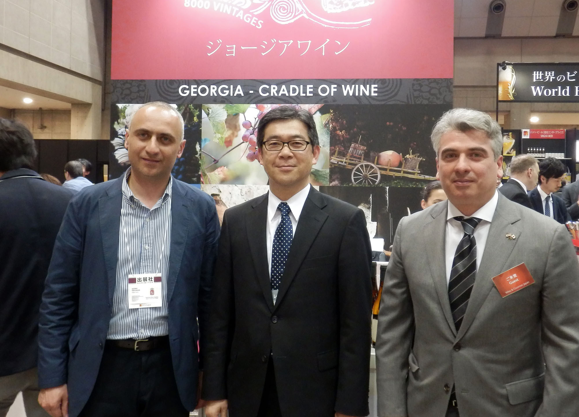 From left, Advisor to Chairman, State Department of Vine and Wine Giorgi Tevzadze, The Japan Times President Takeharu Tsutsumi and Georgian Ambassador Levan Tsintsadze pose in front of the Georgian wine booth following a seminar on Georgia's traditional Qvevri wine making at Wine & Gourmet Japan 2016, at Tokyo Big Sight on April 13. | RINA HASEGAWA