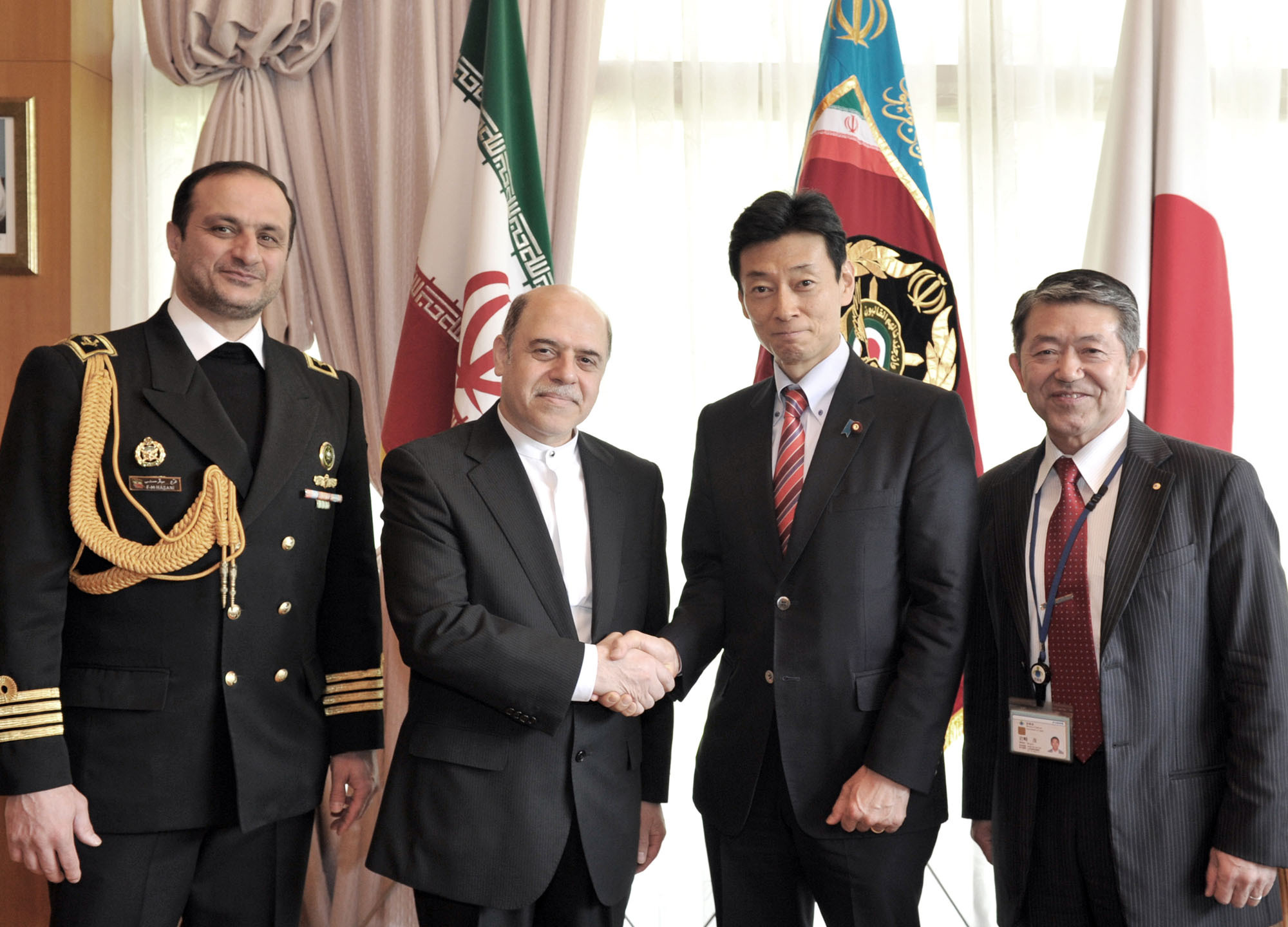 """Iranian Ambassador Reza Nazarahari (second from left) shakes hands with Lower House member Yasutoshi Nishimura. They are flanked by Iranian Military Attache to Japan Capt. Farrokh Movaghar Hassani (left) and Special Adviser to the Minister of Defense Shigeru Iwasaki during a reception to celebrate """"Iran's Armed Forces Day"""" at the embassy in Tokyo on April 15. 