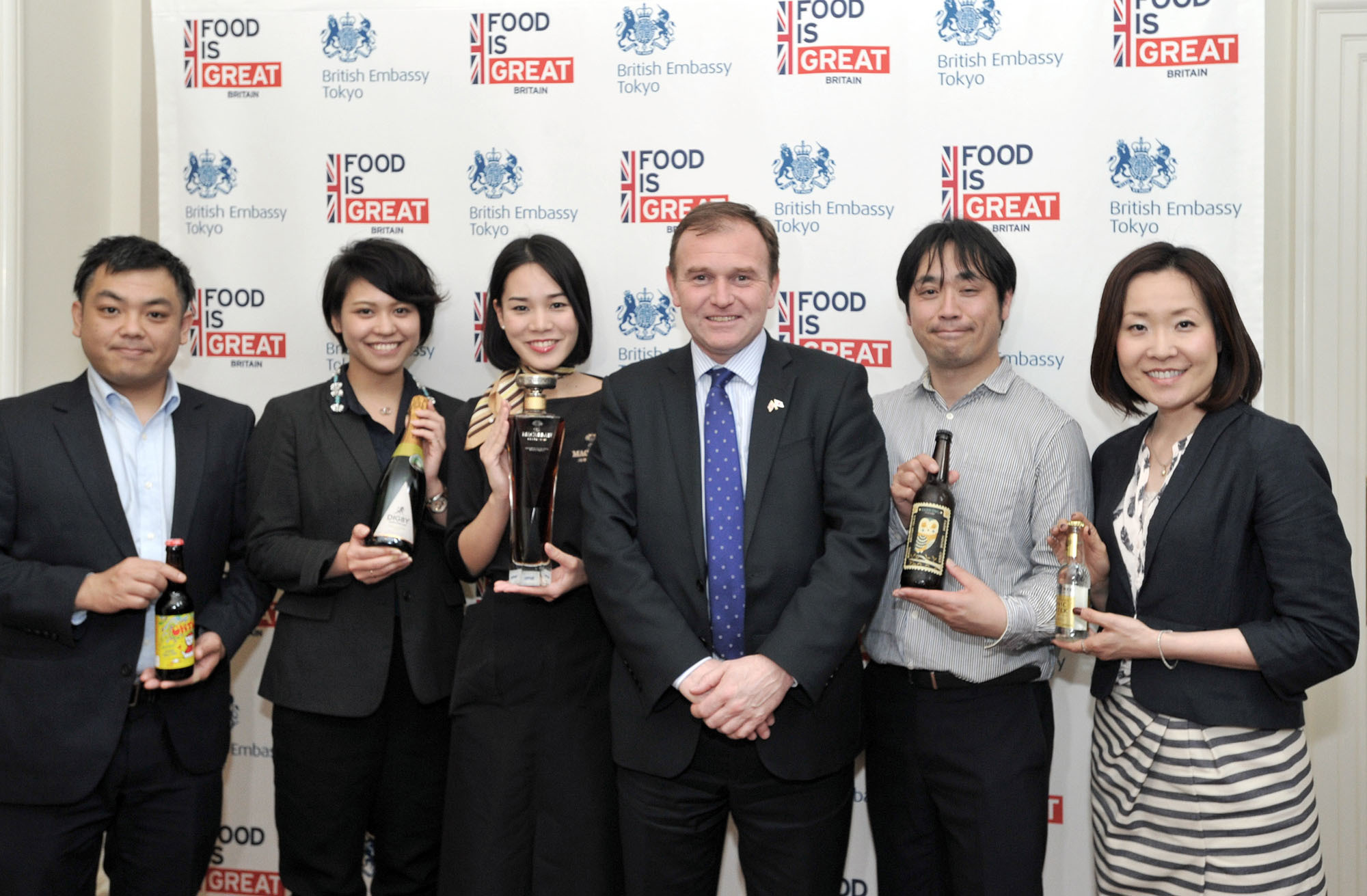 """British Minister of State at the Department for the Environment, Food and Rural Affairs George Eustice (third from right) poses with suppliers representing, from left, Tiny Rebel beer; The British Bottle Company wine; Macallan whisky; Perry's cider; and Sipsmith & Fever-tree gin and tonic, at a """"Food is GREAT,"""" pop-up bar at the British embassy in Tokyo on April 22. 