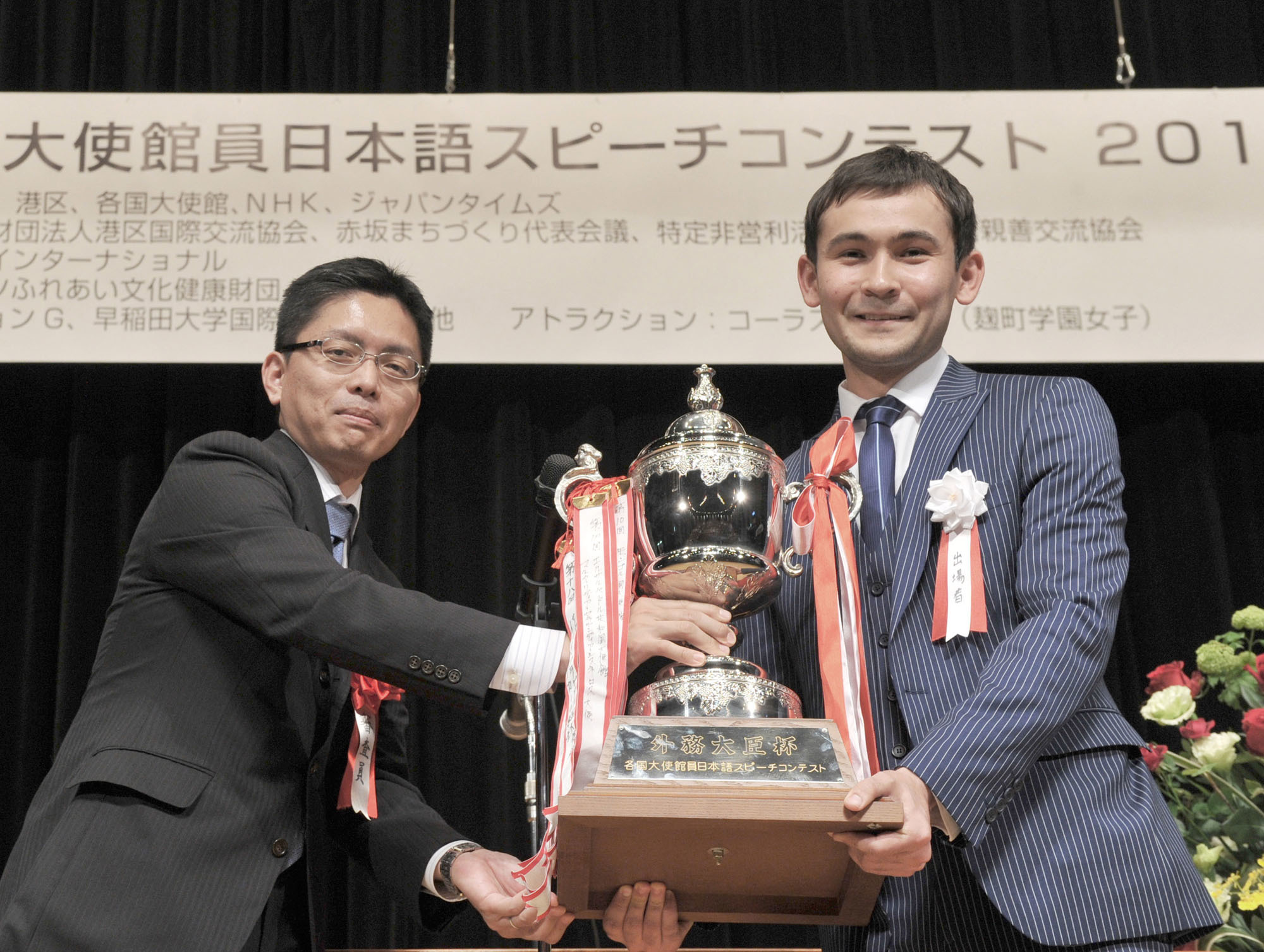 Thirteen contestants from 12 embassies took part in the 19th annual Japanese Speech Contest for Foreign Embassy Officials in Tokyo at the Akasaka Kumin Center on April 23. Fakhriddin Ergashev (Uzbekistan) receives the Foreign Minister's Award from Daisuke Okabe, director of cultural affairs and overseas public relations at the Foreign Ministry. | YOSHIAKI MIURA