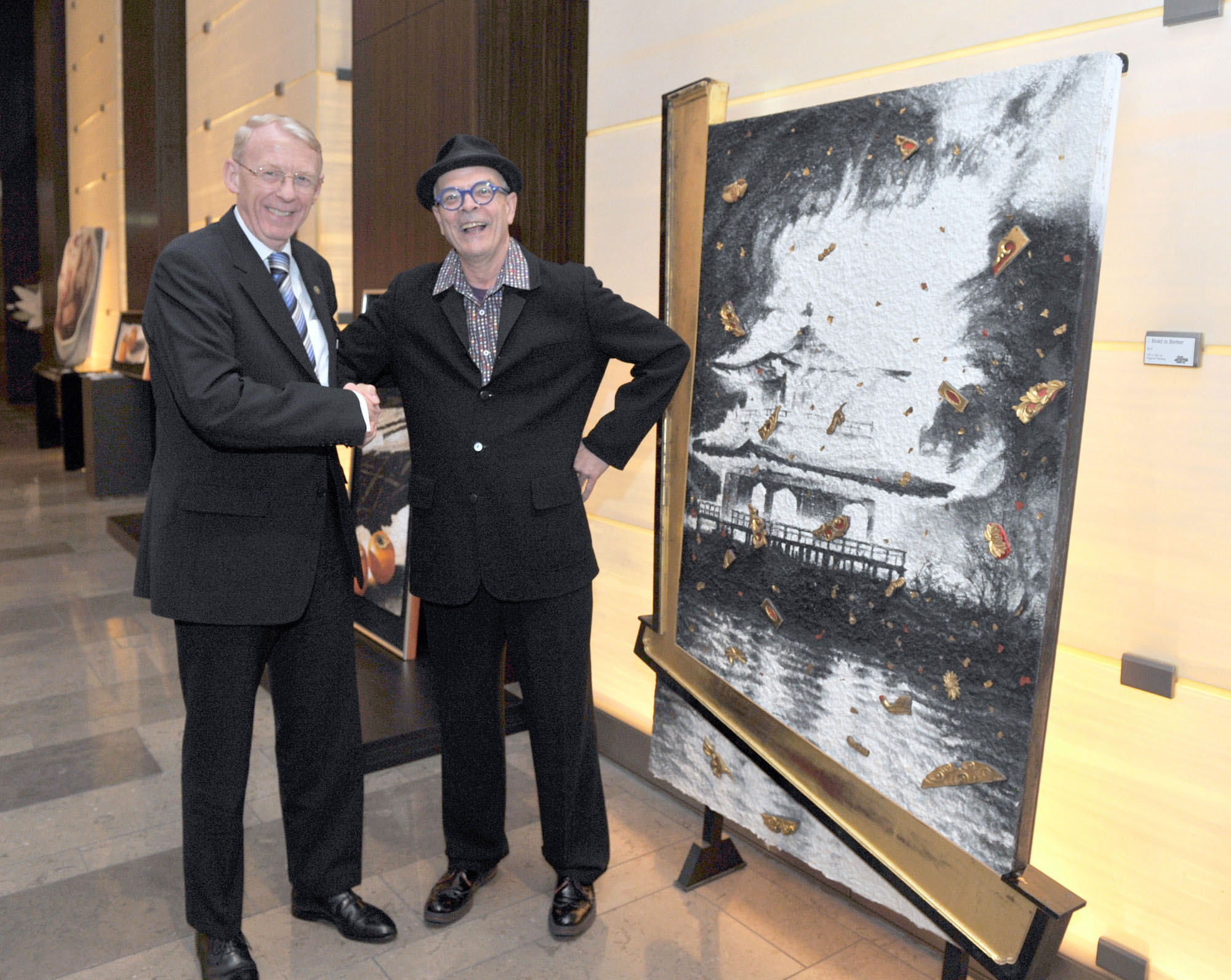 "Kyoto-based American artist Daniel Kelly (right) poses with Heinrich Grafe, general manager of Conrad Tokyo, at the opening April 27 of ""Daniel Kelly's Golden Touch,"" an exhibition of prints and paintings being held at the hotel until May 8 with the help of The Tolman Collection art gallery. 