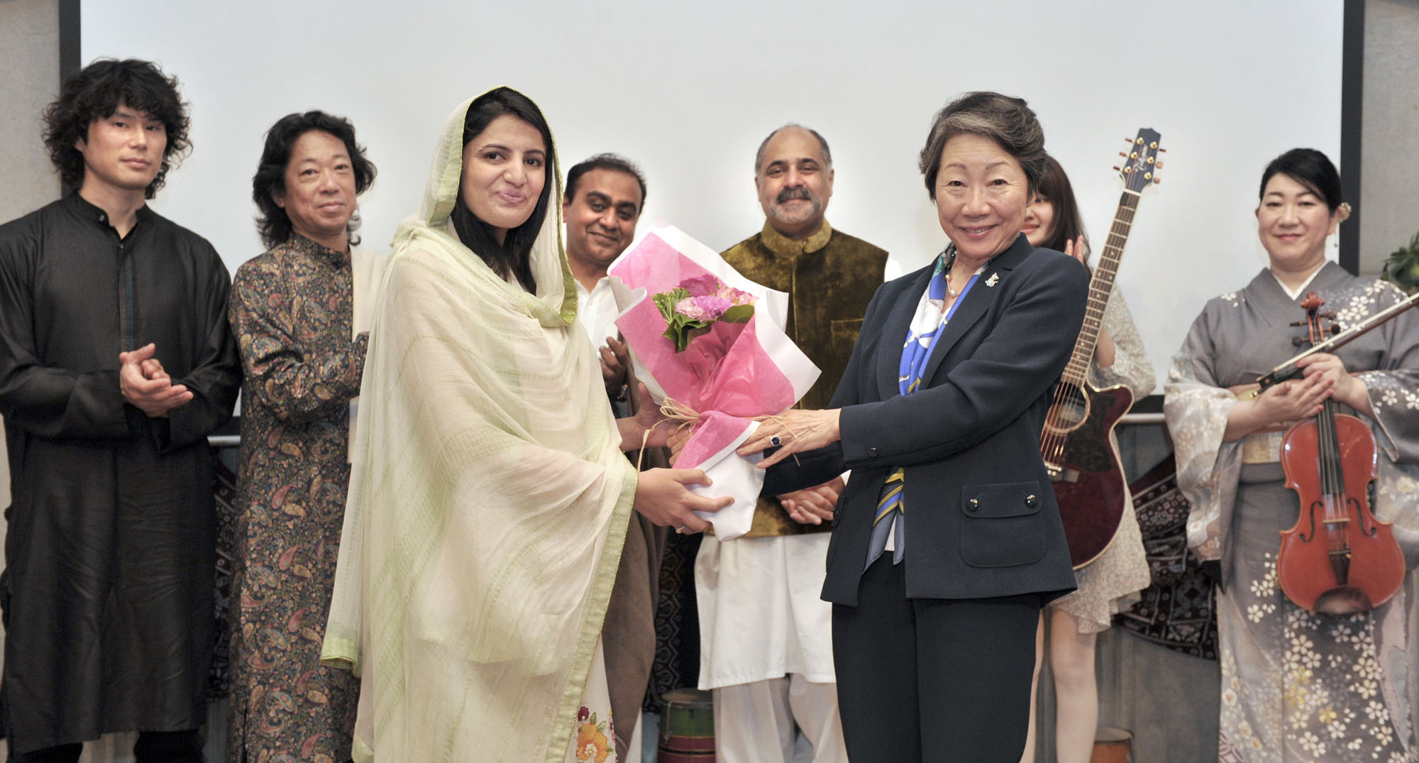 Zaib Malik (left), wife of Shehzad Ahmed Khan, commercial counsellor of the Pakistan Embassy, receives a bouquet from Haruko Komura, president of the Asia-Pacific Ladies Friendship Society (ALFS), on April 28, during the society's Spring Cultural Event 2016 at the Pakistan Embassy. Standing to the left of Komura is Farukh Amil, ambassador of the Islamic Republic of Pakistan. | YOSHIAKI MIURA