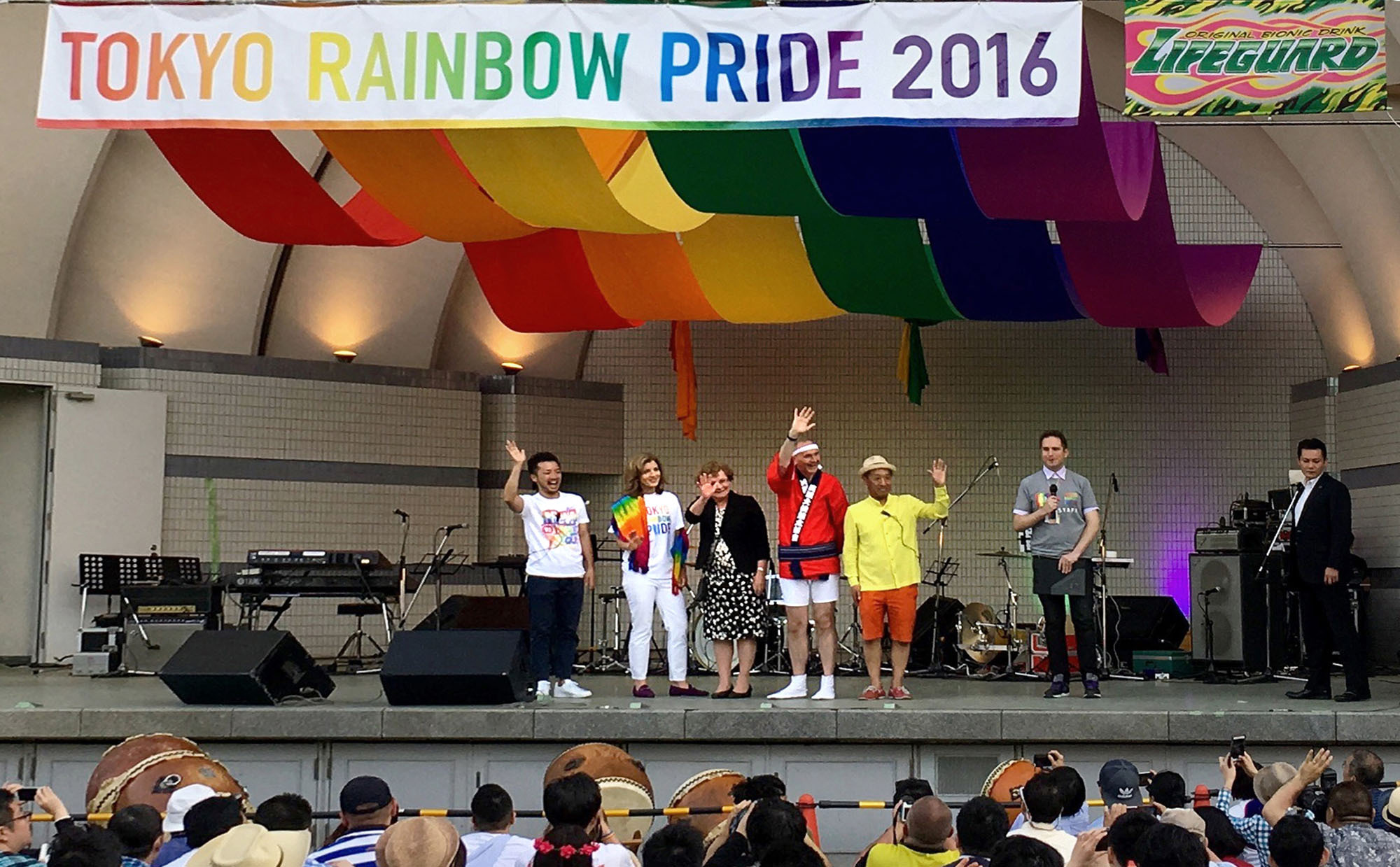U.S. Ambassador Caroline Kennedy (second from left), Irish Ambassador Anne Barrington (third from left), British Ambassador Tim Hitchens (fourth from left) and Tokyo Rainbow Pride Board of Directors co-chairs Fumino Sugiyama (left) and Shinya Yamagata (fifth from left) wave to the audience following the ambassadors' speeches at Tokyo Rainbow Pride 2016, before a British Embassy taiko drum performance at Yoyogi Park in Tokyo on May 8. | BRITISH EMBASSY