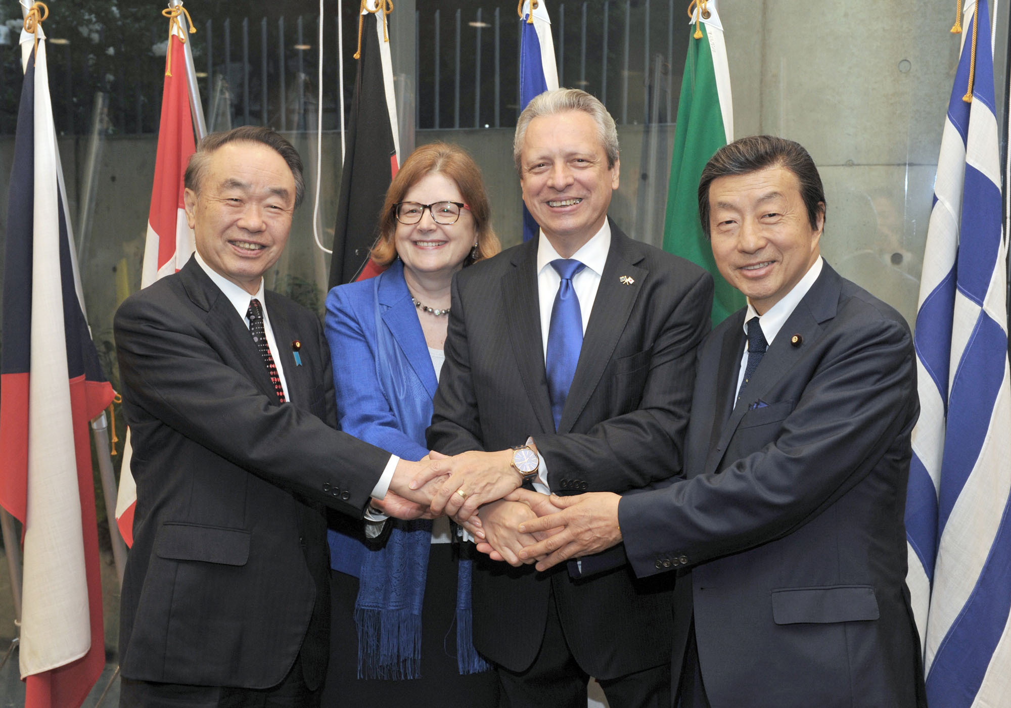 "Viorel Isticioaia-Budura (second from right), the ambassador of the European Union, and his wife Tatiana (second from left) shake hands with State Minister for Internal Affairs and Communications Masatada Tsuchiya (left) and Kenji Kosaka, chairman of the EU-Japan Parliamentary League of Friendship and House of Councillors member at a reception to celebrate ""Europe Day"" at the Delegation of the European Union's Europa House in Tokyo on May 10. 