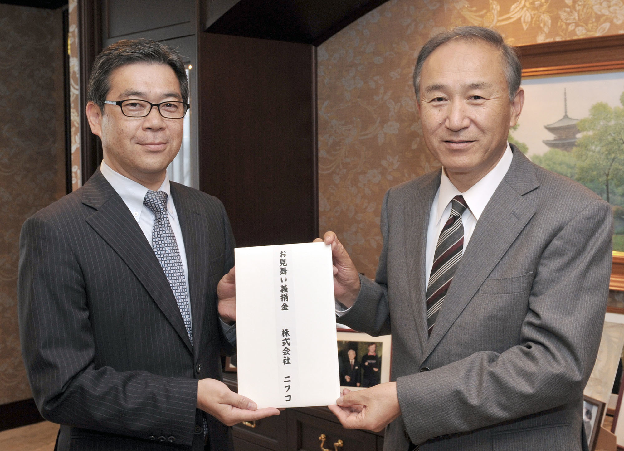 President, Representative Director and Chief Operating Officer of Nifco Inc. Toshiyuki Yamamoto (right) hands The Japan Times President Takeharu Tsutsumi a ¥10,000,000 donation for The Japan Times Readers' Fund that will go to support Kumamoto earthquake victims at the newspaper's headquarters in Tokyo on May 25. | YOSHIAKI MIURA