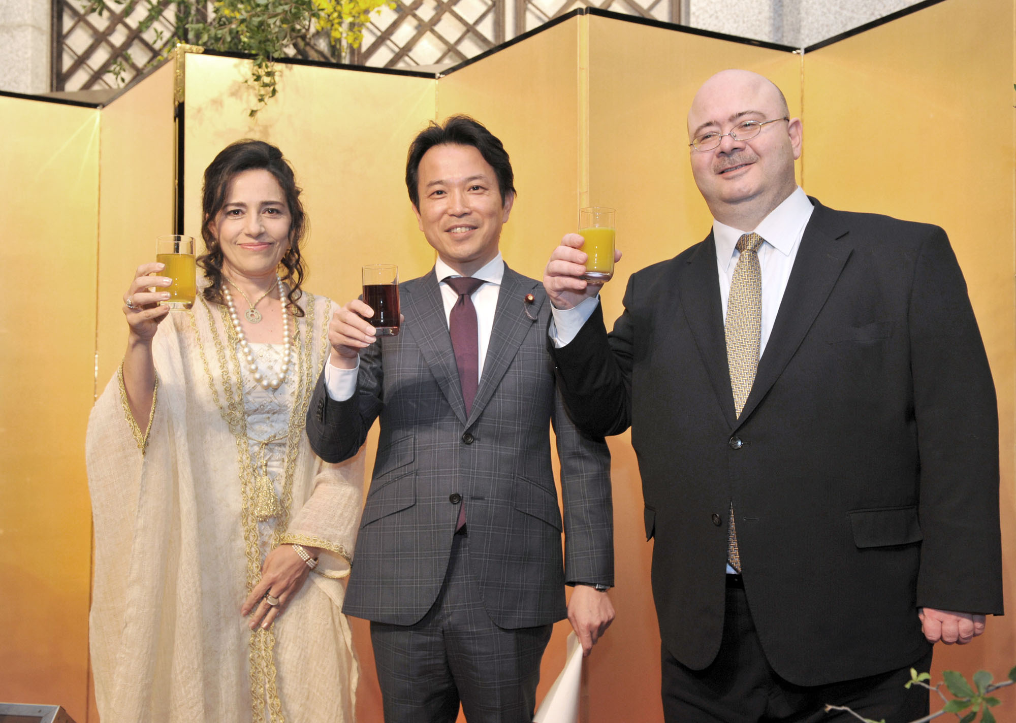 Jordan Ambassador Demiye Haddad (right), and his wife, Shifa (left), share a toast with Parliamentary Vice-Minister for Foreign Affairs Masakazu Hamachi during a reception to celebrate the 70th Anniversary of the country's Independence Day and The Centennial of the Great Arab Revolt, at the Hotel Okura Tokyo on May 25. | YOSHIAKI MIURA