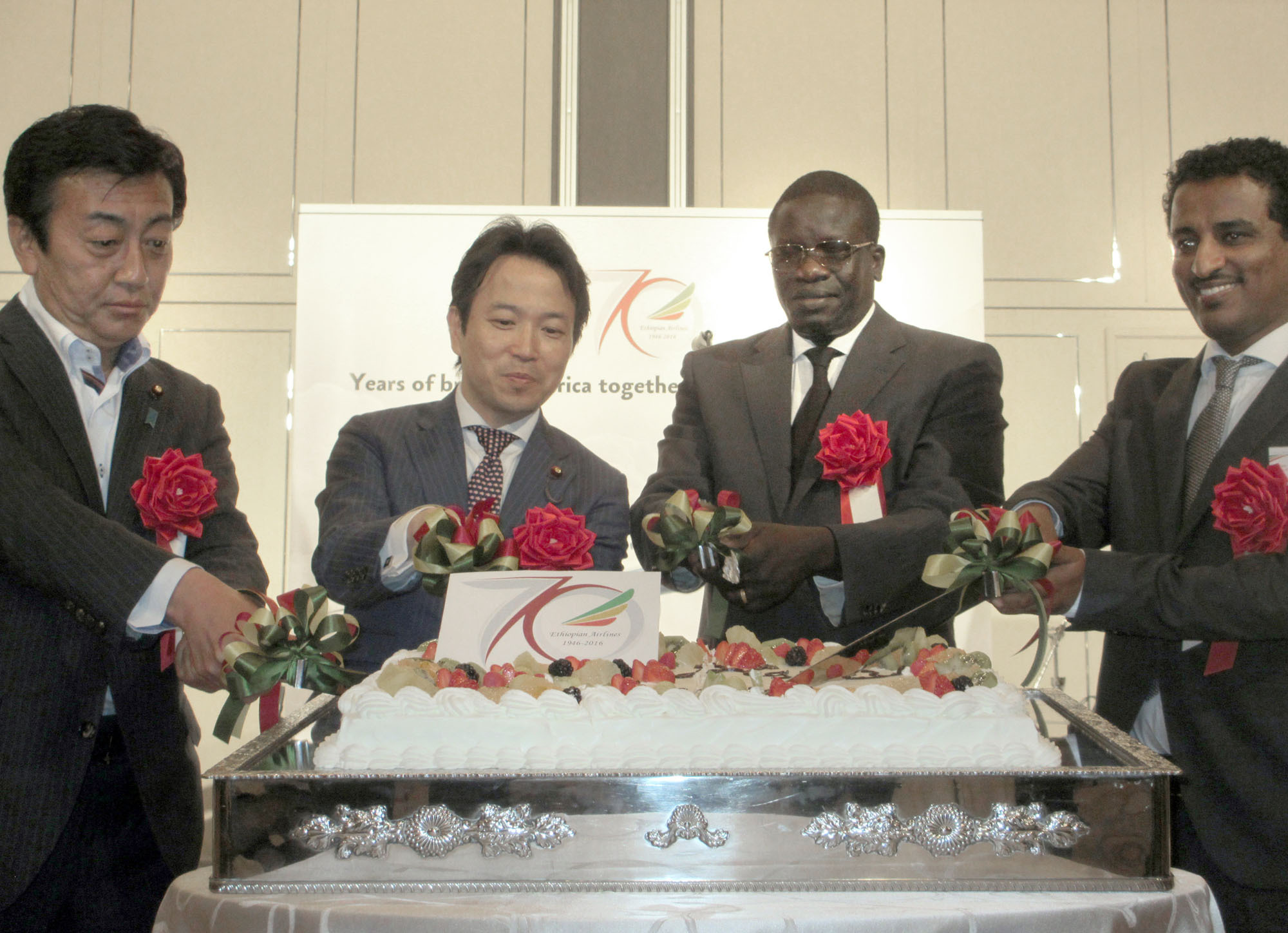 Ethiopian Ambassador Cham Ugala Uriat (second from right) joins, from left, Parliamentary Vice-Minister of Economy, Trade and Industry Tsuyoshi Hoshino; Parliamentary Vice-Minister for Foreign Affairs Masakazu Hamachi; and Ashenafi Yirga, Japan area manager for Ethiopian Airlines, during a cake-cutting ceremony to celebrate the 25th Anniversary of Ethiopian National Day and the 70th Anniversary of Ethiopian Airlines at the Marriott Hotel on May 30. | HIROKO INOUE