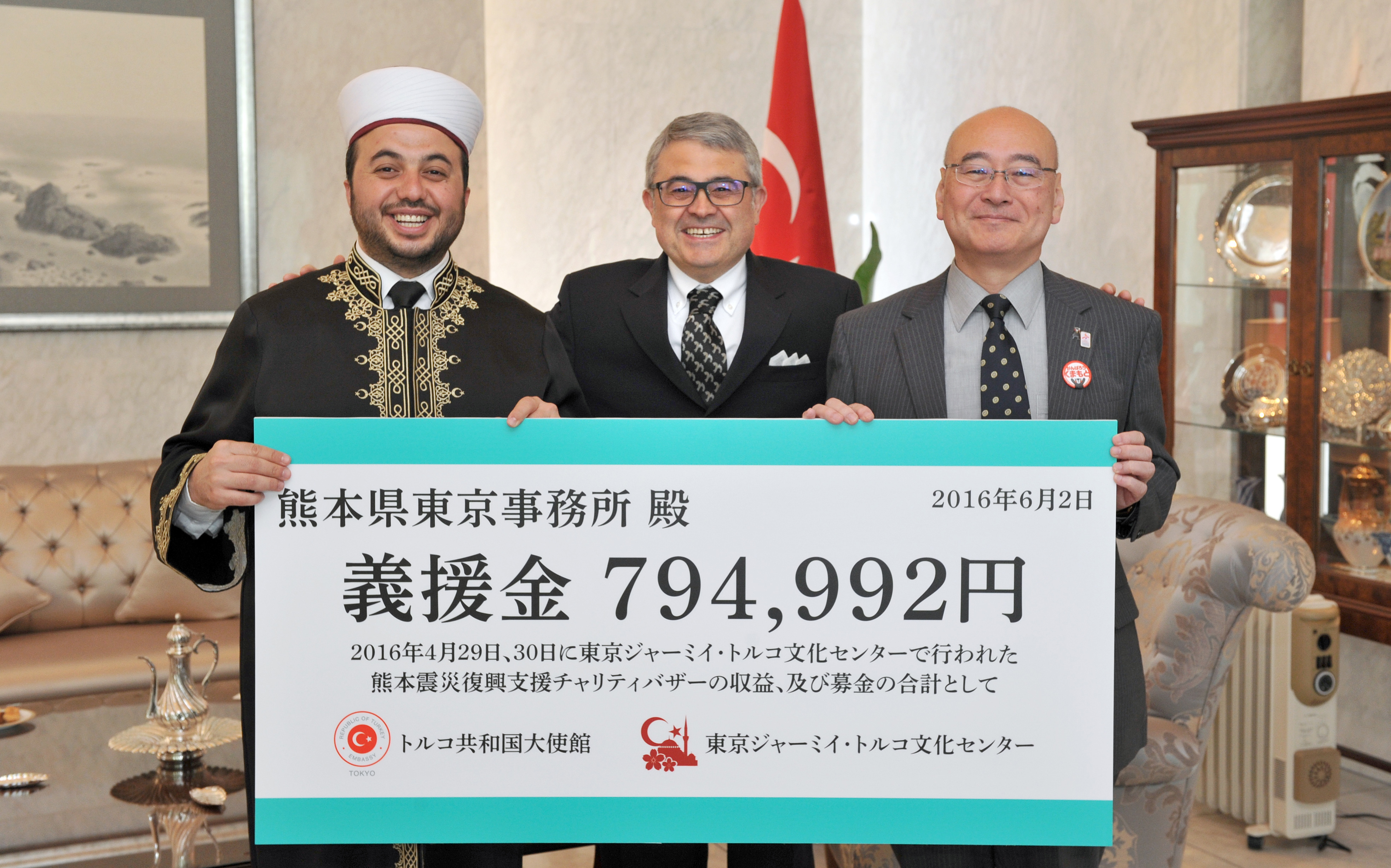 Imam and Director of the Tokyo Camii and Turkish Culture Center Muhammed Rasit Alas (left) and Junichi Watanabe (right), director general of the Tokyo office of the Kumamoto Prefectural Government, are joined by Turkish Ambassador Ahmet Bulent Meric as the center presents the prefecture with a ¥794,992 donation, raised from the proceeds of a Kumamoto earthquake reconstruction charity bazaar, at the Turkish Embassy in Tokyo on June 2. | YOSHIAKI MIURA