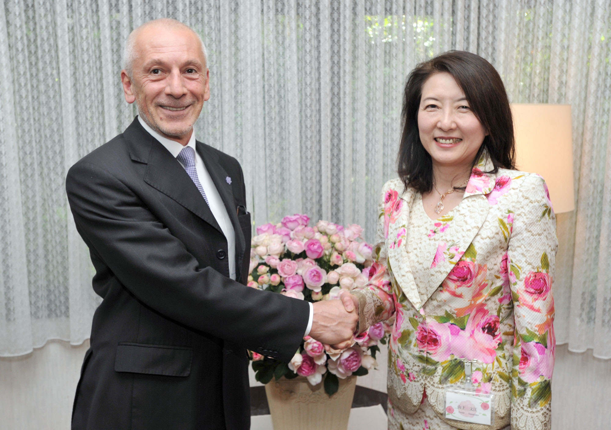 Bulgarian Rose Cultural Association Director Fumie Yamashita (right) shakes hands with Bulgarian Ambassador Georgi Vassilev at the second Rose Day Charity Party at the ambassadors residence in Tokyo on June 2. | YOSHIAKI MIURA