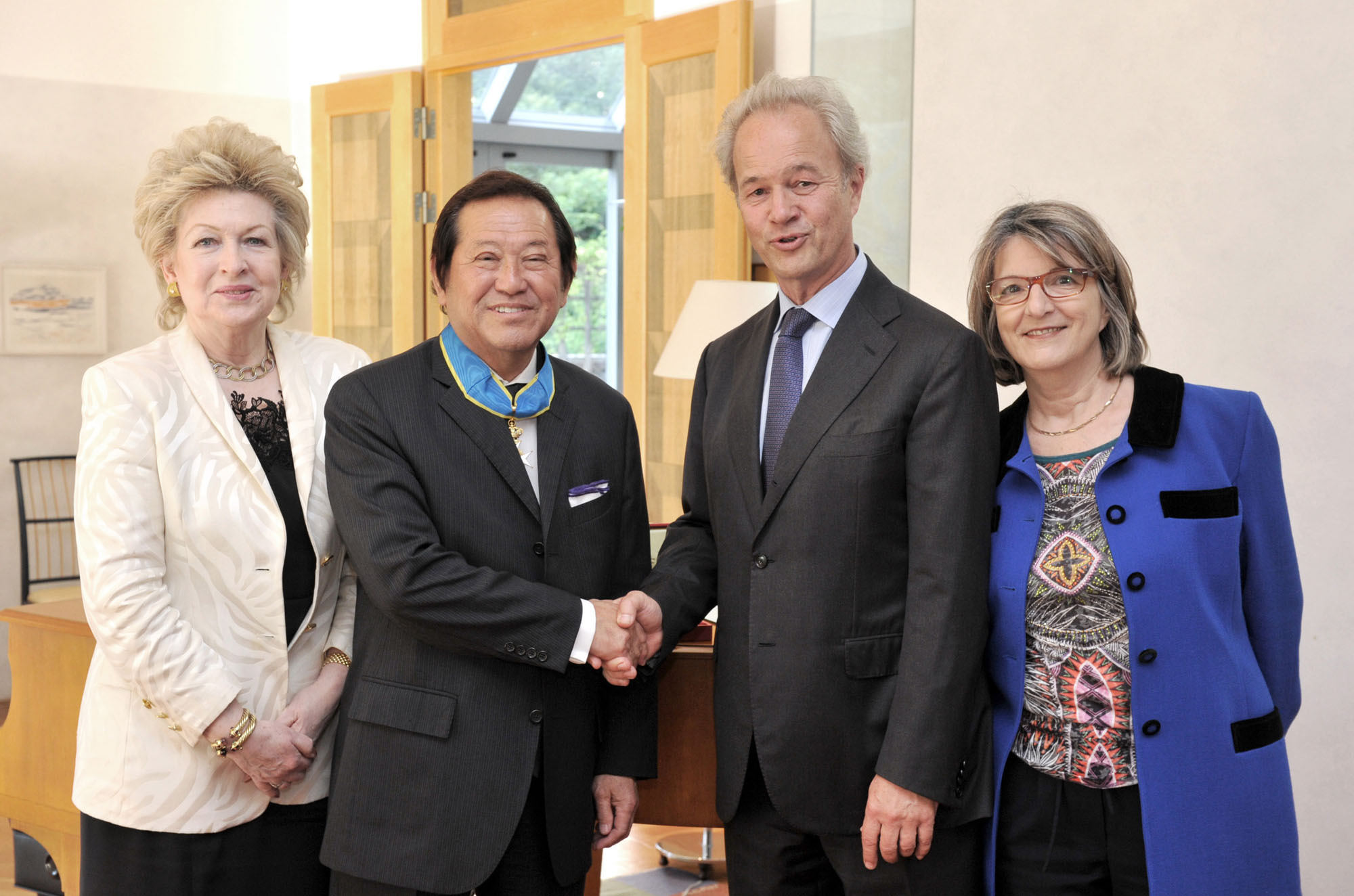 Swedish Ambassador Magnus Robach (second from right) shakes hands with Honorary Consul in Nagano Soichiro Yoshida, after presenting him with the insignia of Commander of Order of the Polar Star for his long service, flanked by Yoshida's wife, Carole (left) and the ambassador's wife, Michele, at the embassy in Tokyo on June 3. | YOSHIAKI MIURA