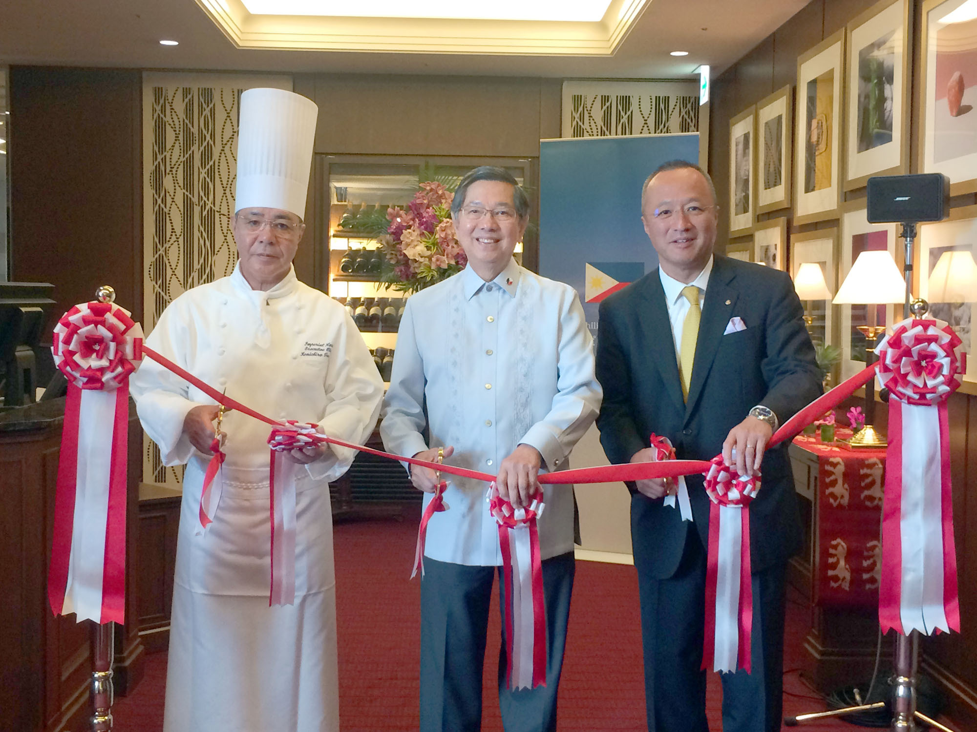 "Philippine Ambassador Manuel M. Lopez (center) joins Grand Chef of the Imperial Hotel Kenichiro Tanaka (left) and Imperial Hotel President and General Manager Hideya Sadayasu at a ribbon-cutting ceremony for the ""Philippine Fiesta"" dining promotion, which runs through June 19 at the Imperial Viking Sal restaurant, at the Imperial Hotel, Tokyo, on June 13. 