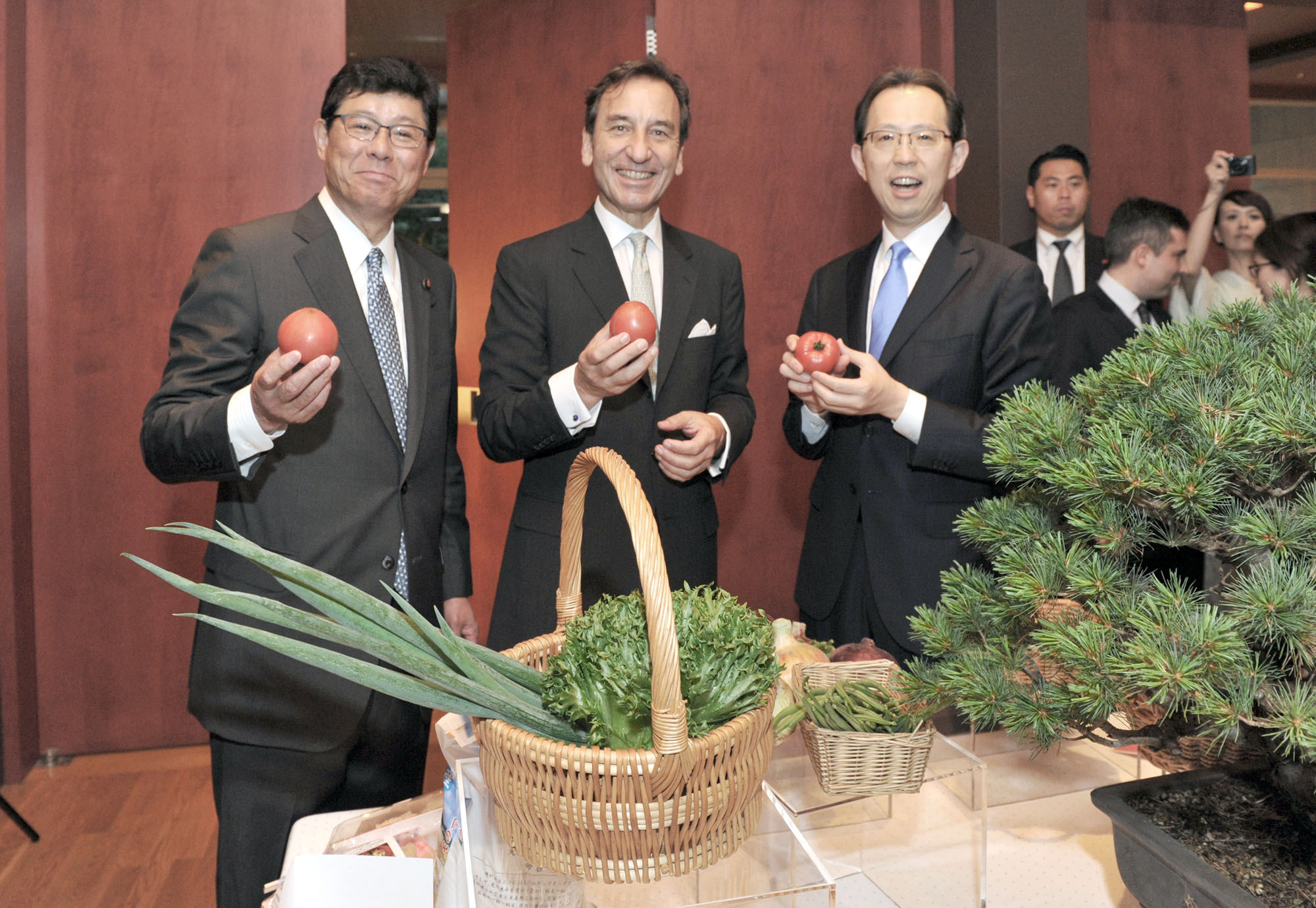 "French Ambassador Thierry Dana (center), Reconstruction Minister, Minister in charge of Revival from the Nuclear Accident at Fukushima Tsuyoshi Takagi (left) and Fukushima Prefecture Gov. Masao Uchibori hold fresh produce from the prefecture at a press conference before the ""DINER D'AMITIE FRANCE FUKUSHIMA"" (France-Fukushima friendship dinner), which aims to revitalize the region. 