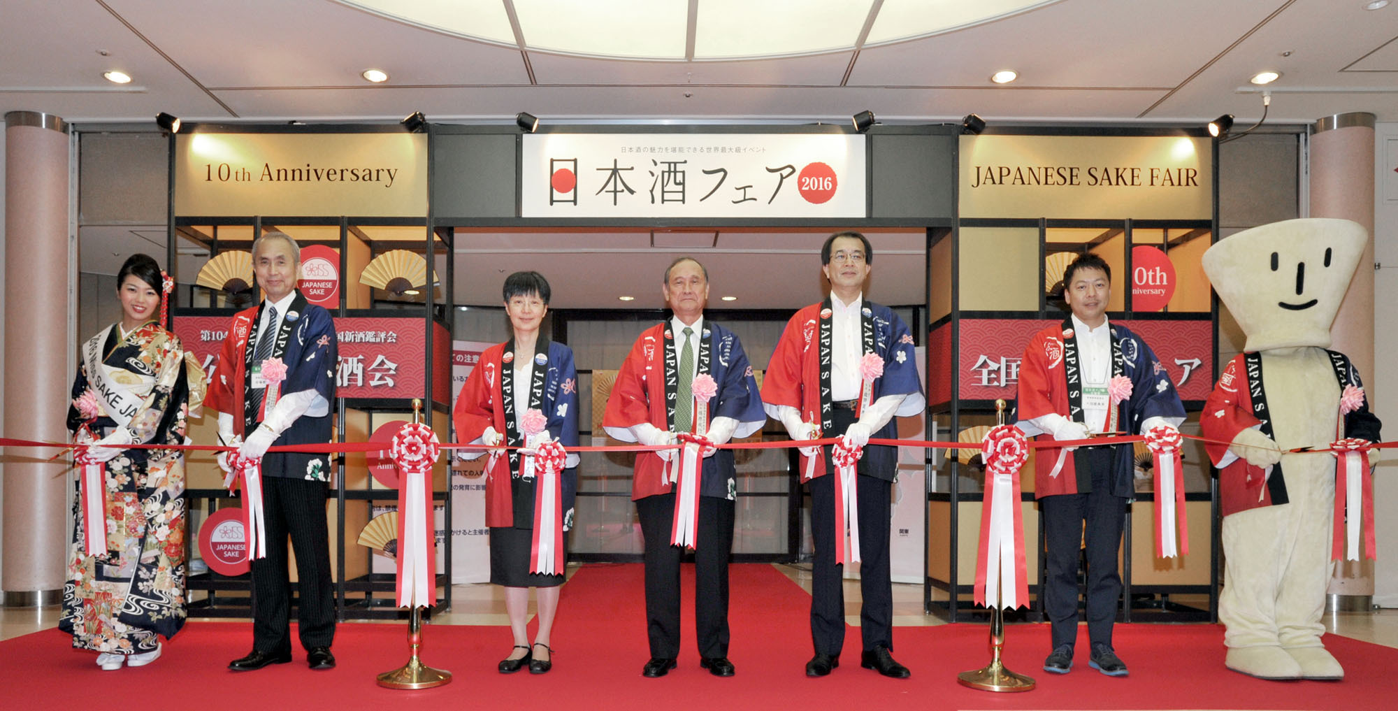 (From left) Miss Sake Japan Sayuri Tanaka; Tohoku Meijo Co. President Junji Sato; National Research Institute of Brewing President Nami Goto; Japan Sake and Shochu Makers Association Chairman Shigeyuki Shinohara; National Tax Agency Commissioner Hidenori Sakota; Tenzan Sake Brewery Chairman Kensuke Shichida; and mascot Ochoko-kun cut the ribbon to kick off the 10th Anniversary of the Japanese Sake Fair, the Japan Sake Brewers Association's annual public sake tasting event in the Sunshiine City complex in the Ikebukuro district of Tokyo on June 18. | YOSHIAKI MIURA