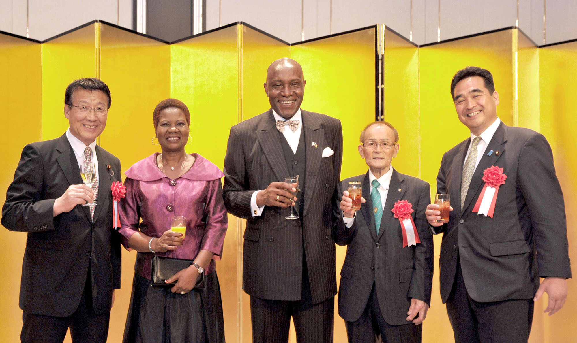 Cameroon Ambassador Pierre Ndzengue (center) prepares to make a toast with (from left) Asahiko Mihara, member of the House of Representatives; the ambassador's wife Alphonsine; Yasumu Sakamoto, former Nakatsue mayor and present director of the Nakatsue Village Earth Foundation; and State Minister for Financial Affairs Manabu Sakai at a reception to celebrate the country's 44th National Day at the Marriott Hotel in Tokyo on June 20. | YOSHIAKI MIURA