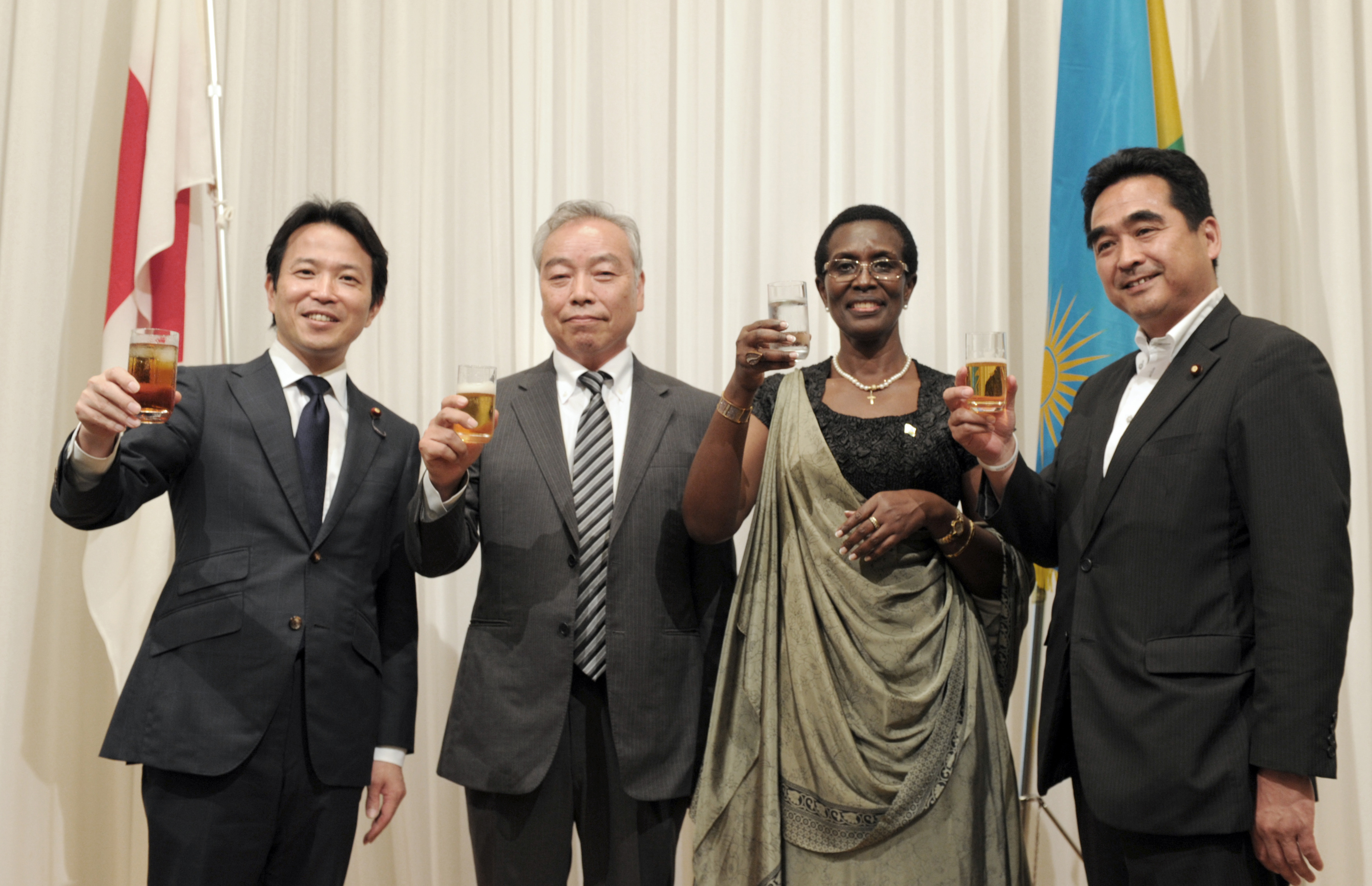 Rwandan Ambassador Venetia Sebudandi (second from right) prepares for a toast with, from left, Parliamentary Vice-Minister for foreign Affairs Masakazu Hamachi; Specialty Coffee Association of Japan President Shinji Sekine; and State Minister of Finance and Secretary-General of the Japan-Rwanda Parliamentary League of Friendship Manabu Sakai during a reception to celebrate the country's Liberation Day and Independence Day at the Toshi Center Hotel, in Tokyo on July 4. | YOSHIAKI MIURA