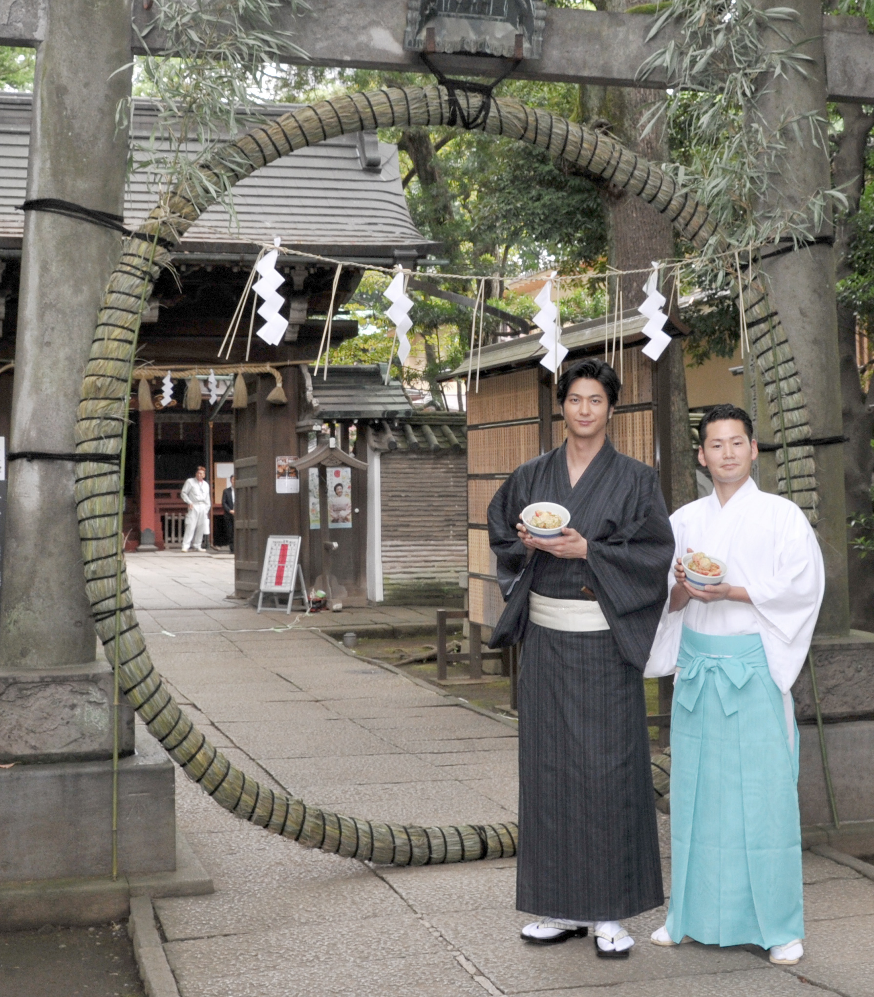 "Artist Mokomichi Hayami (left) and Akasaka Hikawa Shrine's Sotaro Kamiya pose with nagoshi-gohan, or nagoshi rice, at a ""Nagoshi no Harae"" Shinto half-year purification ritual promotion event, in front of a chino-wa ring of reeds, during a press conference at the shrine on June 29. 