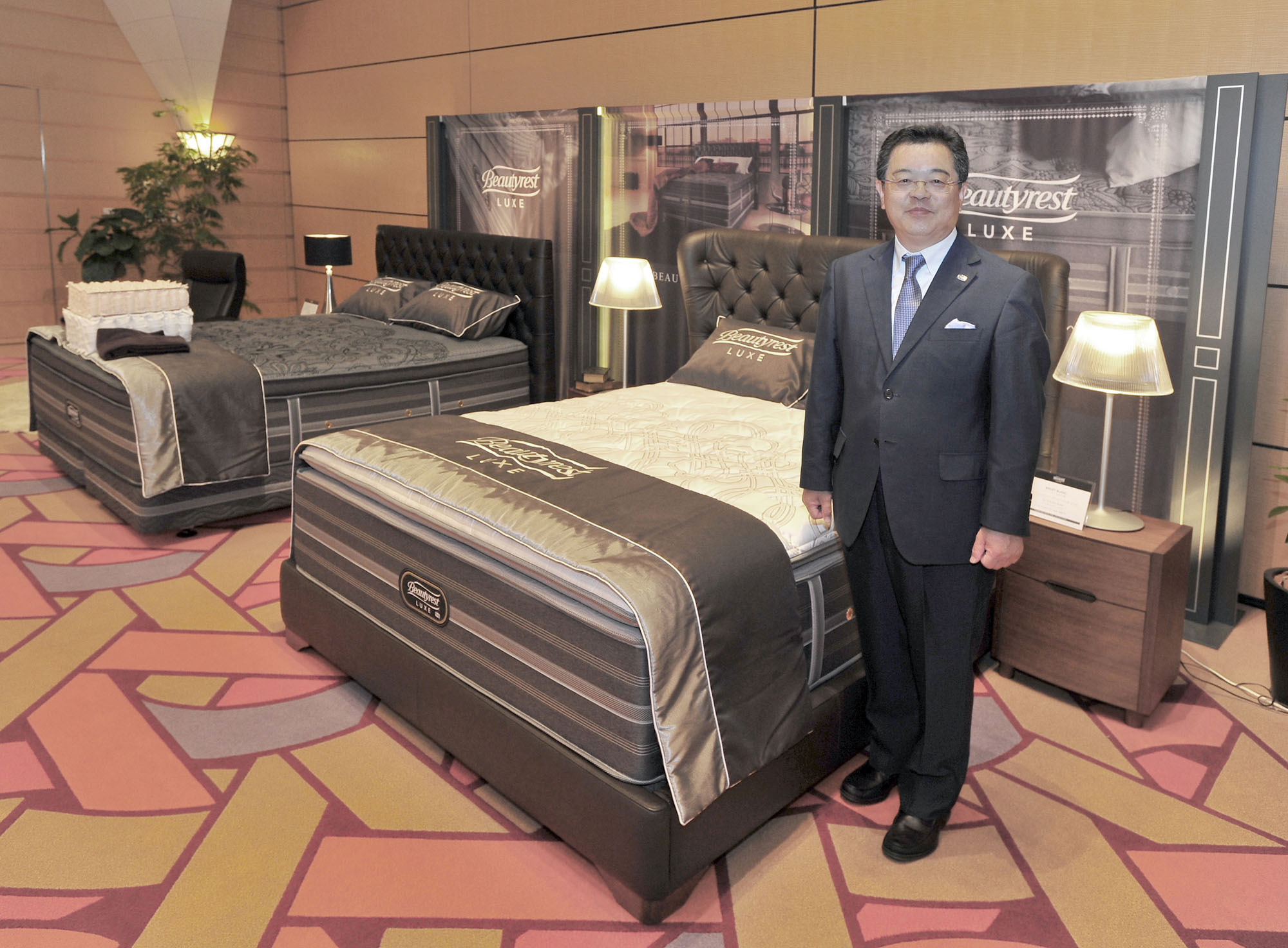 "Simmons Co. President Masafumi Ito poses next to Simmons' new ""Gran Pillow Top"" from the ""Beautyrest Luxe"" series an event introducing Simmons' 2016-17 lineup at the Tokyo American Club on July 20. 