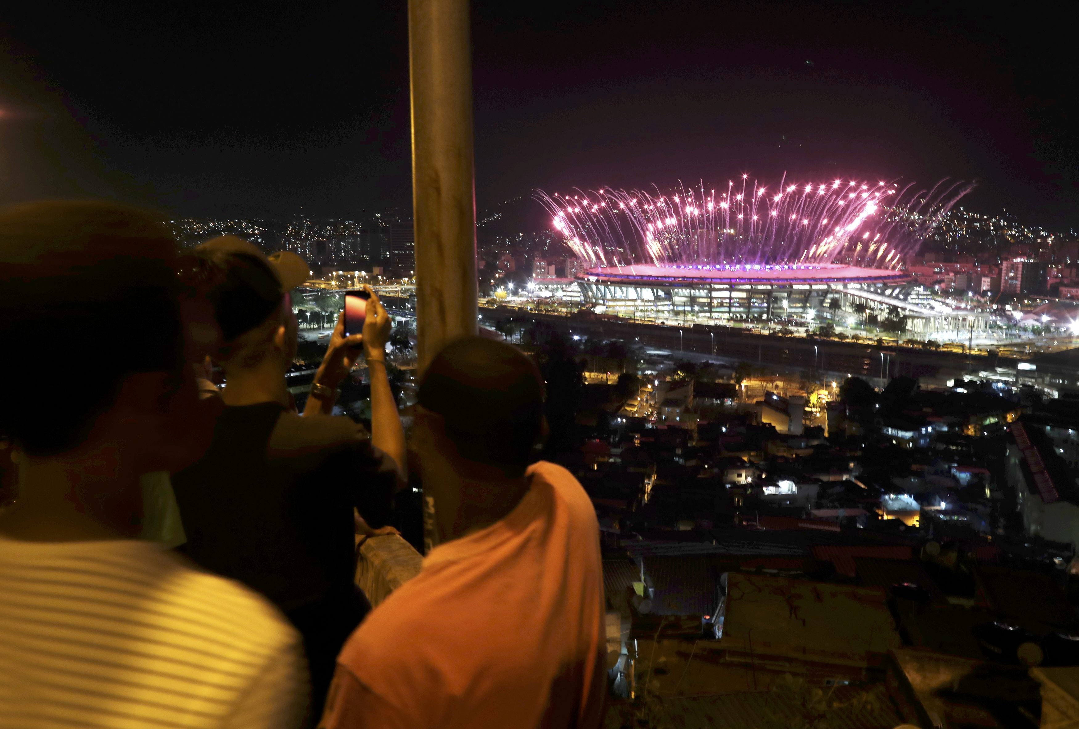 People watch fireworks explode over the Maracana Stadium from the roof of their home in the Mangueira favela, or slum, as the Olympic Opening Ceremony unfolds. |  REUTERS