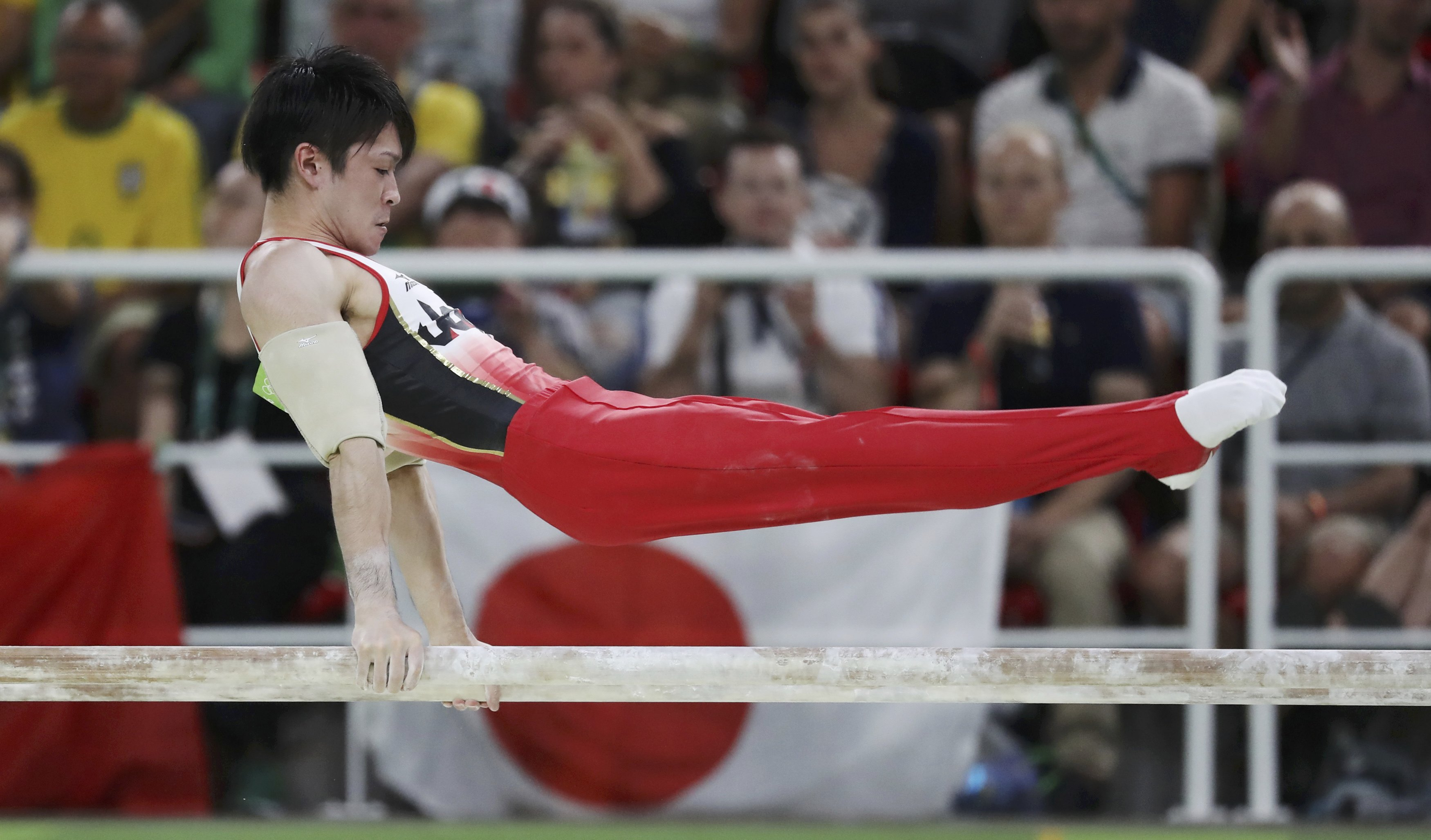 Kohei Uchimura competes on the parallel bars during the men's gymnastics team final en route to winning the gold medal on Monday at the 2016 Rio de Janeiro Olympics. | REUTERS