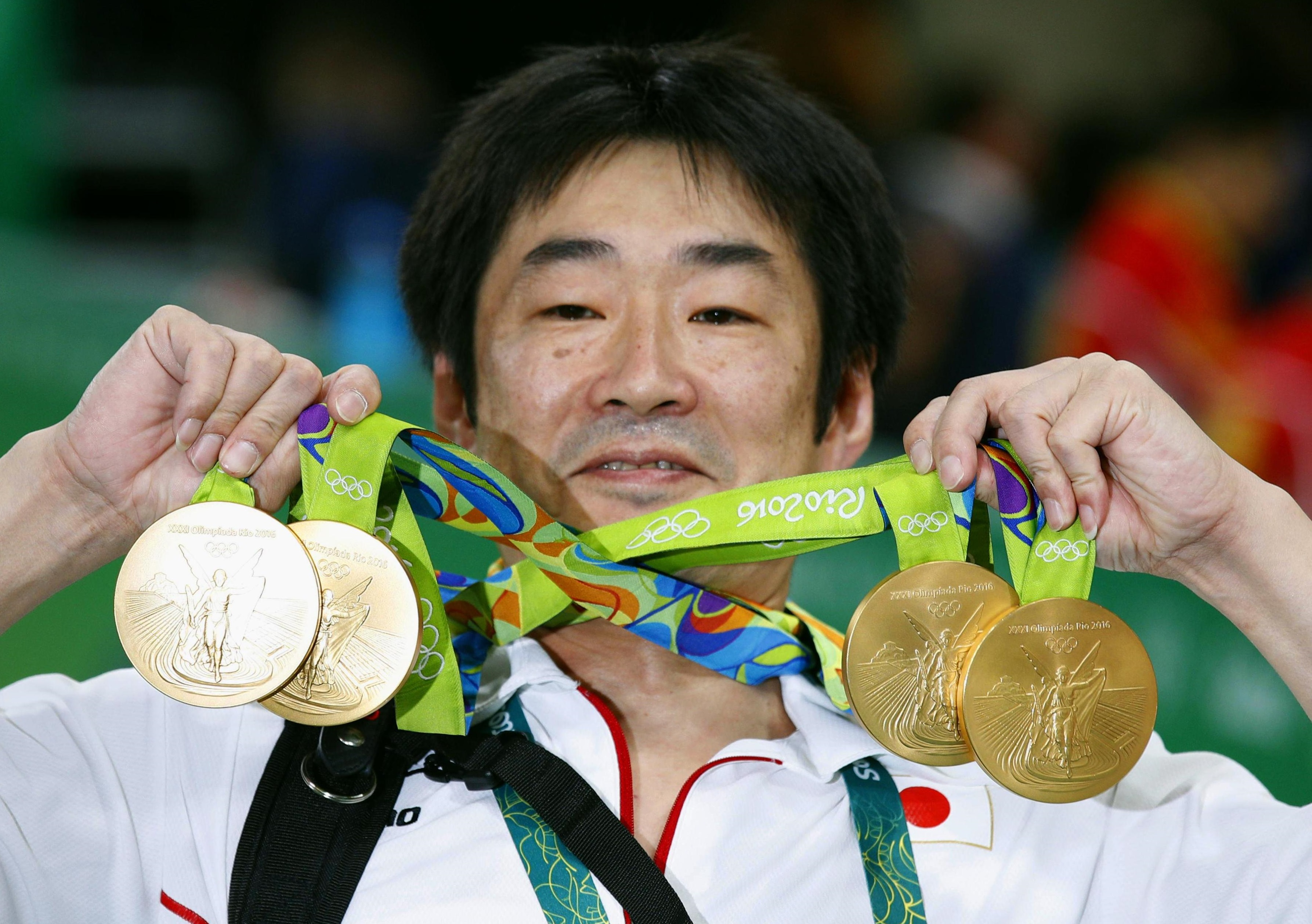 Japan gymnastics coach Takahiro Moriizumi shows off the gold medals after the Japanese team won the men's team event on Monday at the 2016 Summer Olympic Games in Rio de Janeiro. | KYODO