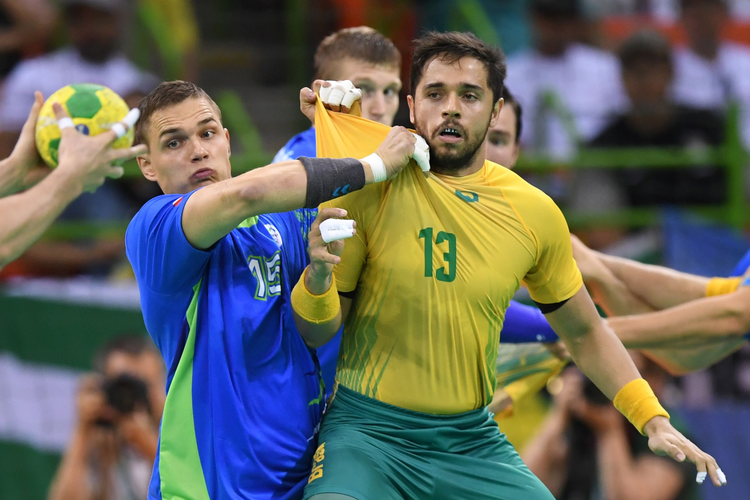 Slovenia's pivot Vid Poteko (left) vies with Brazil's center back Diogo Kent Hubner during their preliminary contest in men's handball at the Rio de Janeiro 2016 Olympics Games at the Future Arena on Tuesday.  | AFP-JIJI