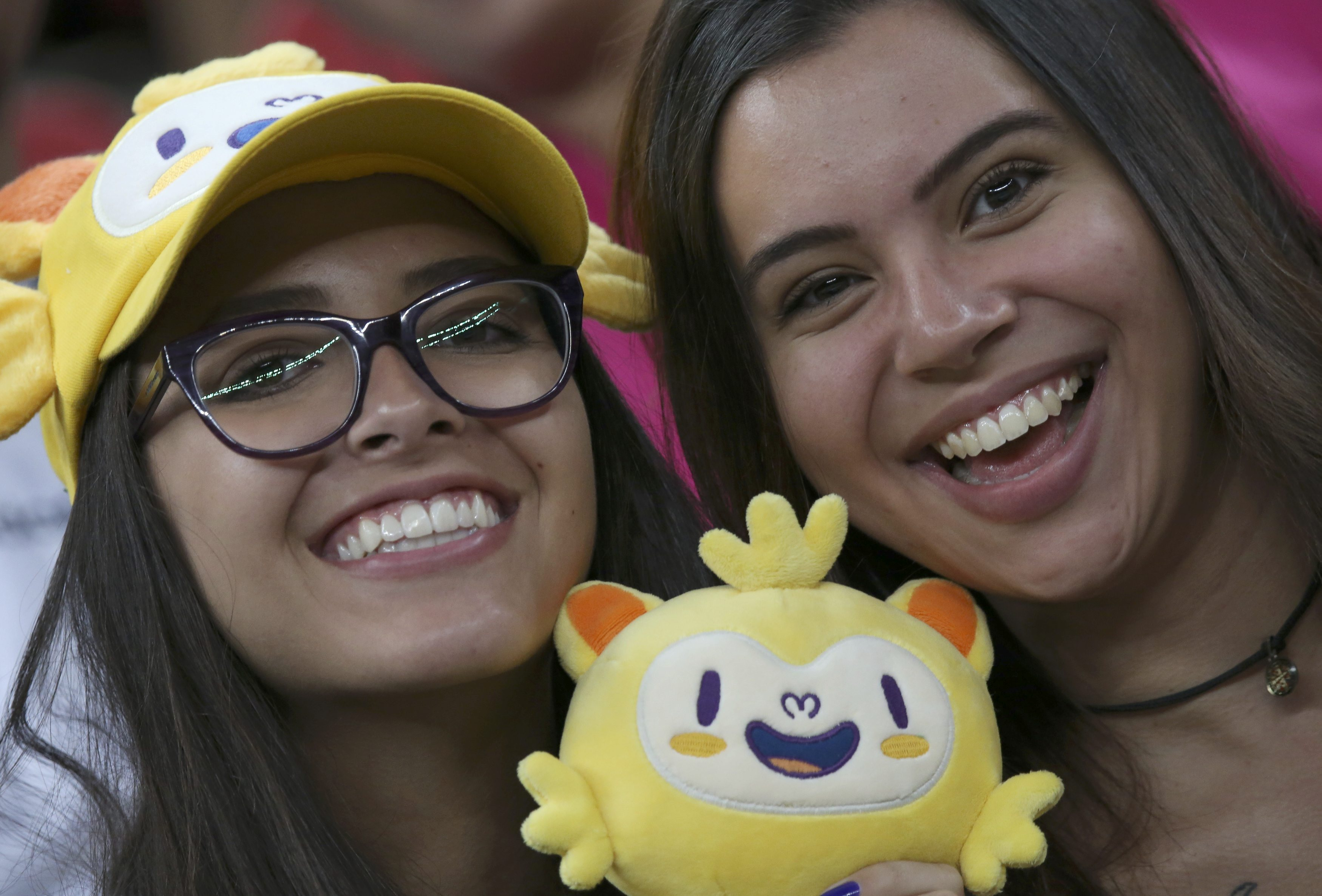 Female fans enjoy a women's soccer game between Sweden and China holding an Olympic mascot on Tuesday at Mane Garrincha Stadium. | REUTERS