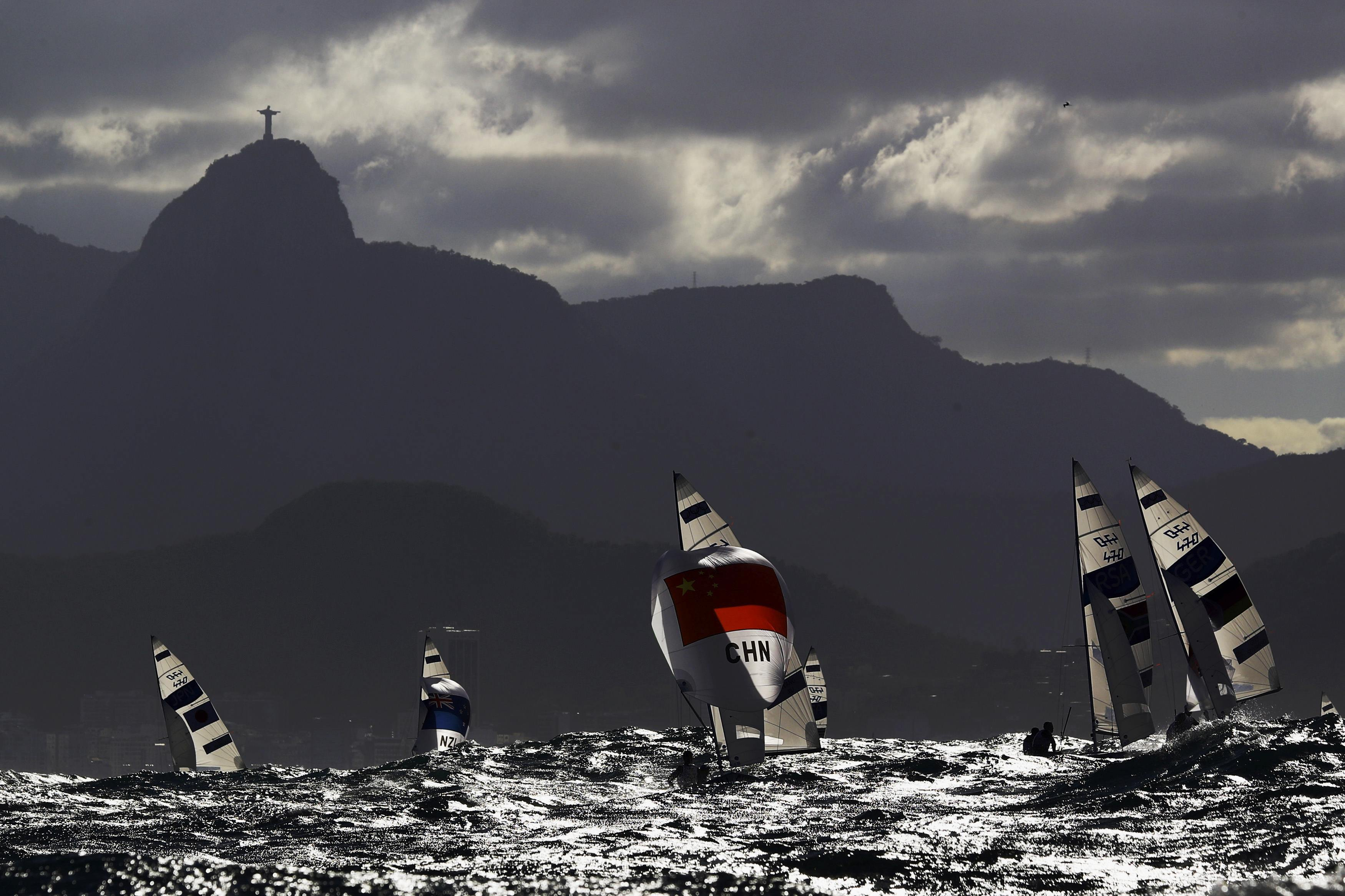 Sailors compete under the Christ the Redeemer statue during Thursday's preliminary round for the men's two-person dinghy at the Rio de Janeiro Olympics.  | REUTERS