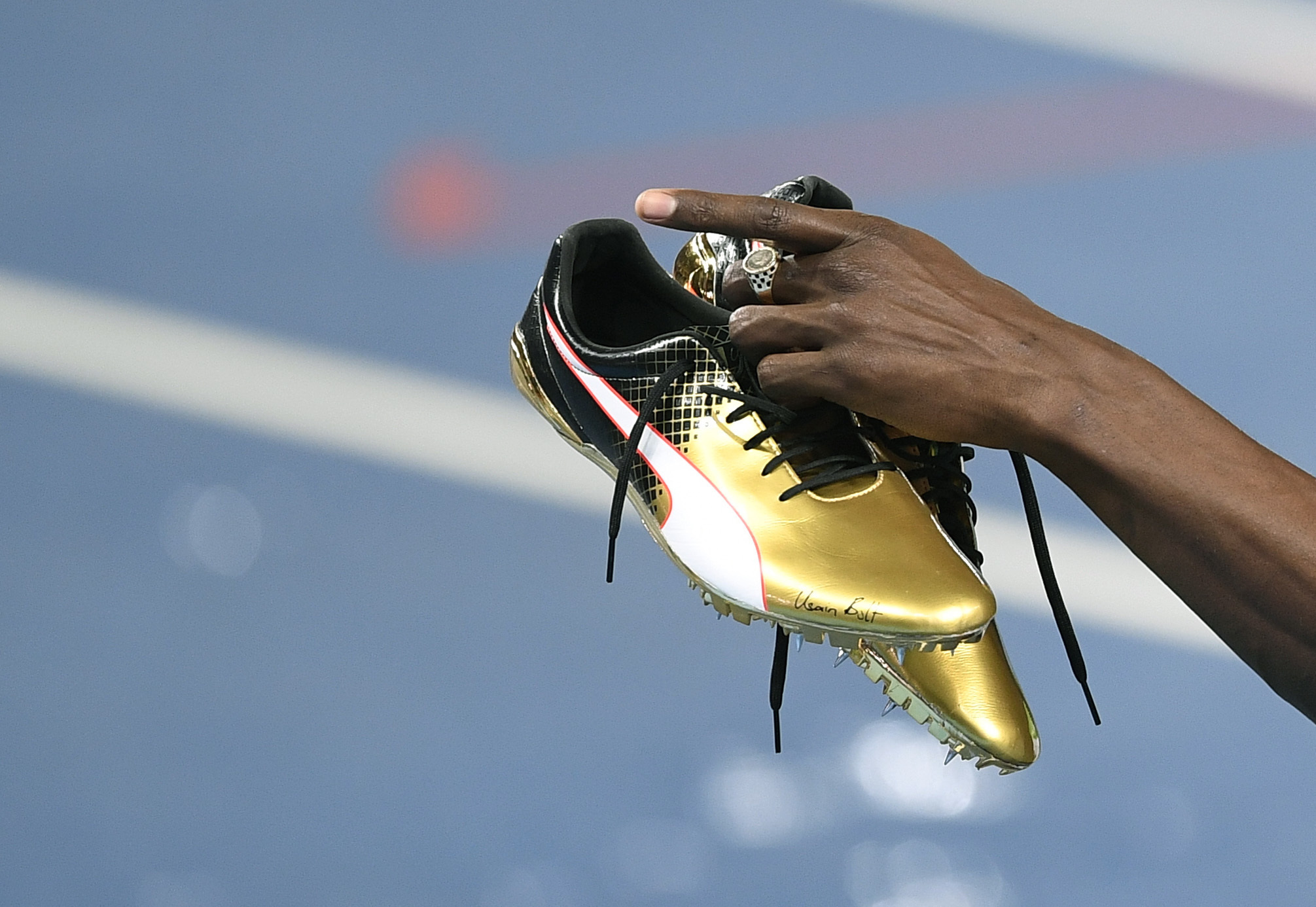 Jamaica's Usain Bolt holds up his shoes after winning the men's 100-meter final during on Sunday at the 2016 Summer Olympics in Rio de Janeiro.   AP